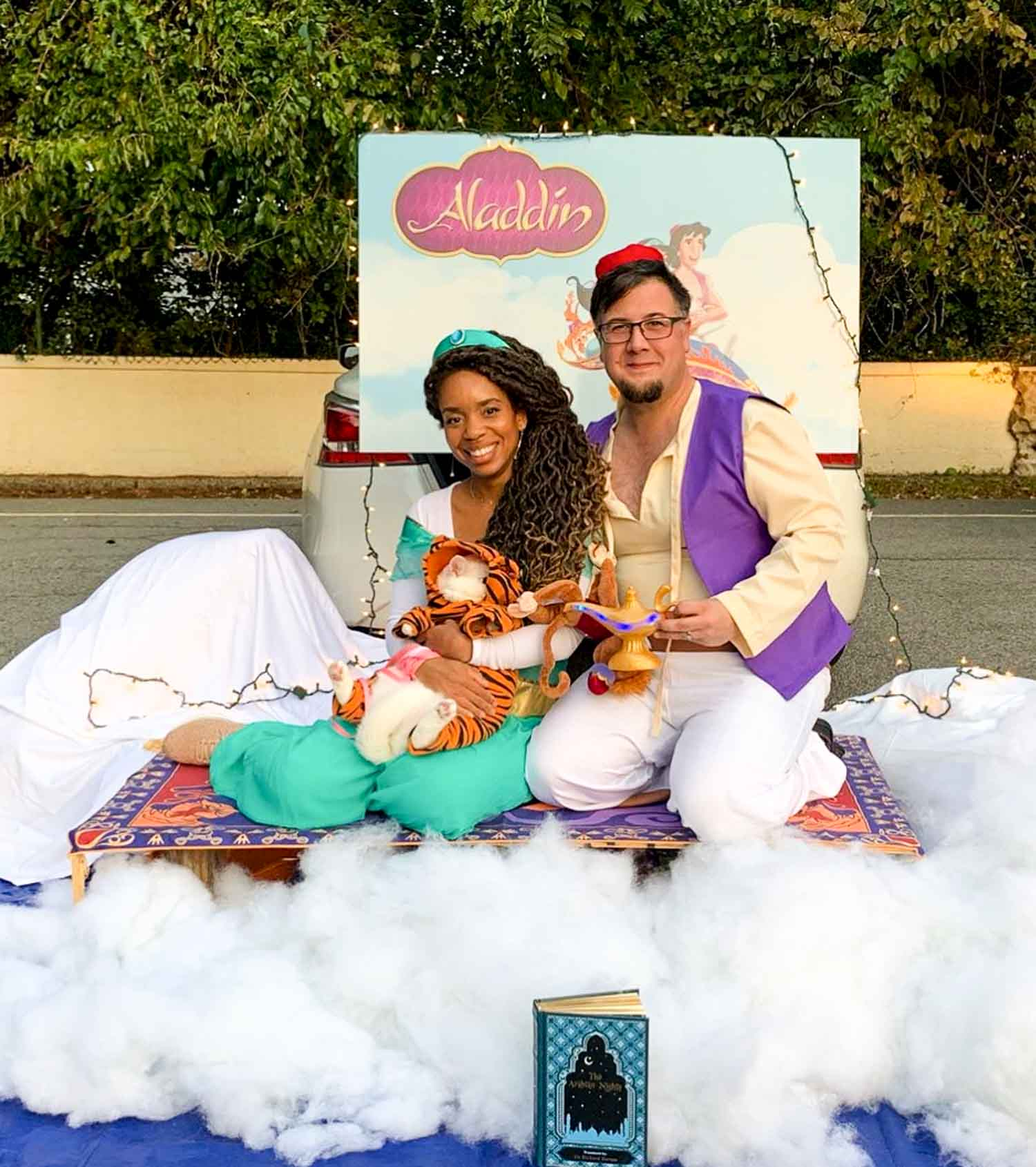 An Aladdin themed setting with people dressed up as characters sitting on a rug with clouds underneath them.