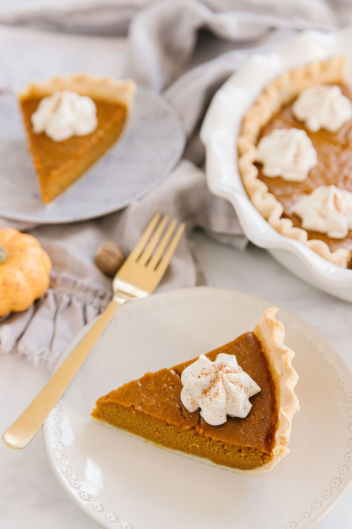 A white plate with a pumpkin pie wedge with a dollop of whipped cream on it with a gold fork on it. Behind is another pie piece on a plate and the rest of the pie in a white pan.