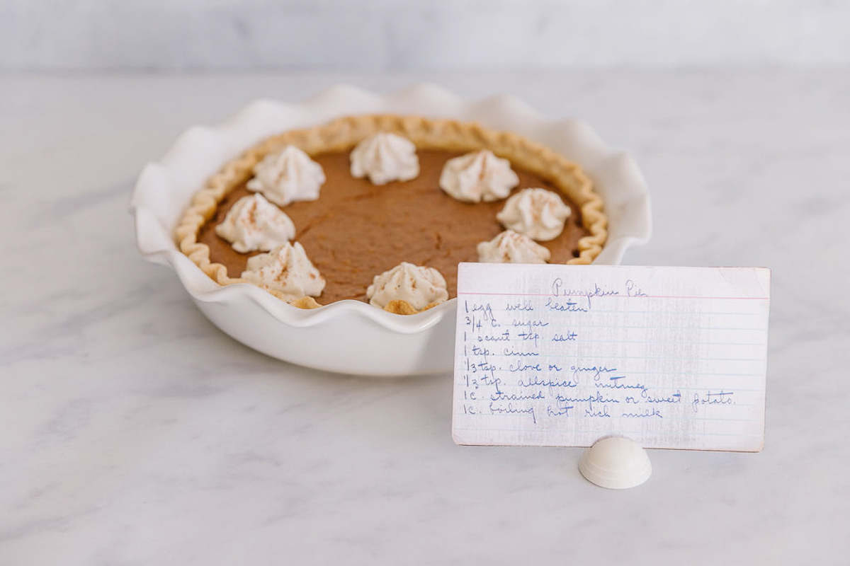 A white pan holding a whole fresh pumpkin pie with whipped cream dollops on it with a handwritten recipe card in front.