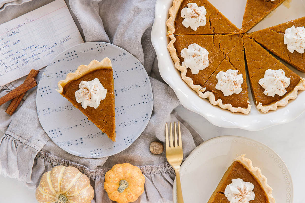 A blue plate with a pumpkin pie piece with whipped cream and a handwritten recipe card behind it with a white plate with another piece of pumpkin pie with a gold fork while the rest of the pie sits behind in a white pan.
