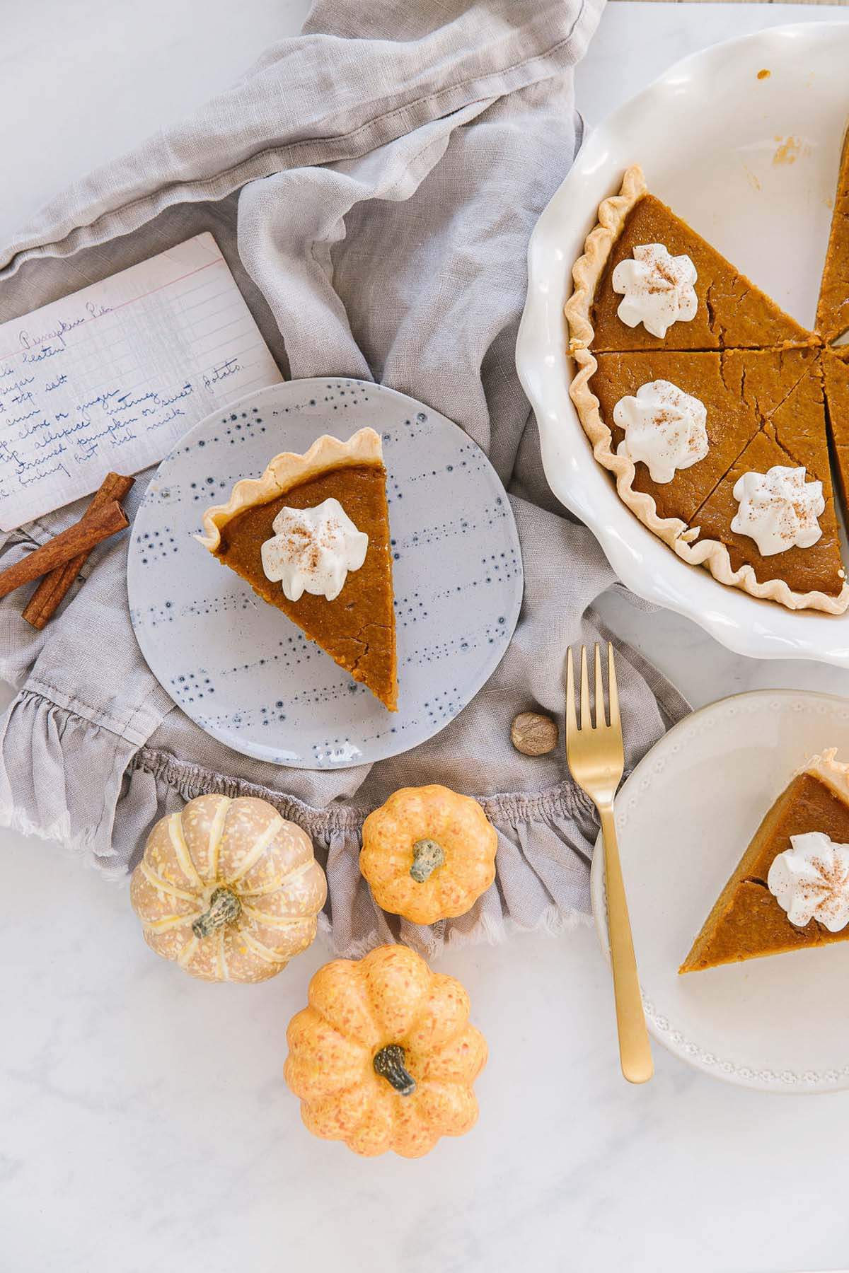 A blue plate with a pumpkin pie piece with whipped cream and a handwritten recipe card behind it with a white plate with another piece of pumpkin pie with a gold fork while other pieces of pie sit in a white pan.
