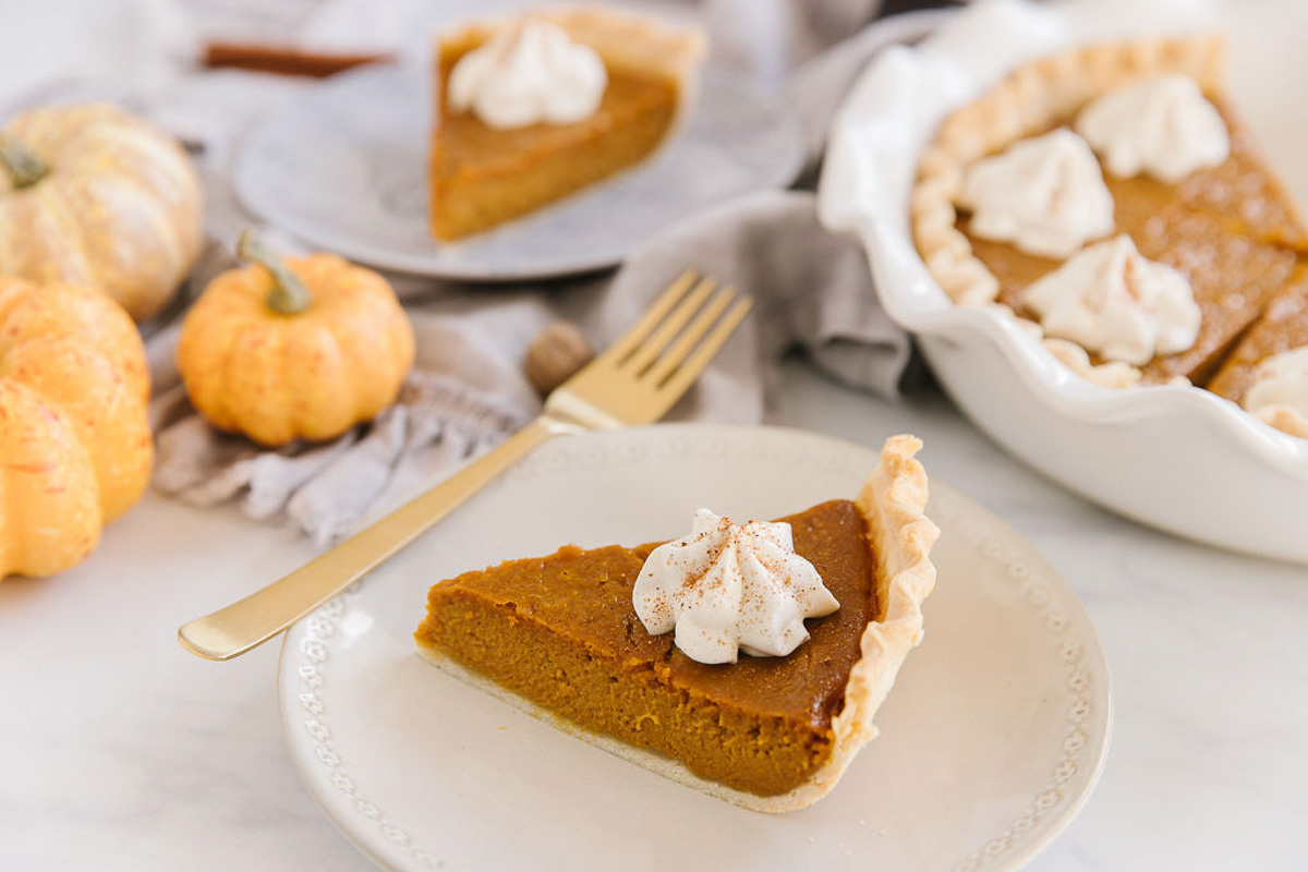 A white plate with a piece of fresh pumpkin pie with whipped cream on it with a gold fork. Behind are mini pumpkins, a blue plate holding another pumpkin pie slice and a white pan of other pumpkin pie slices.