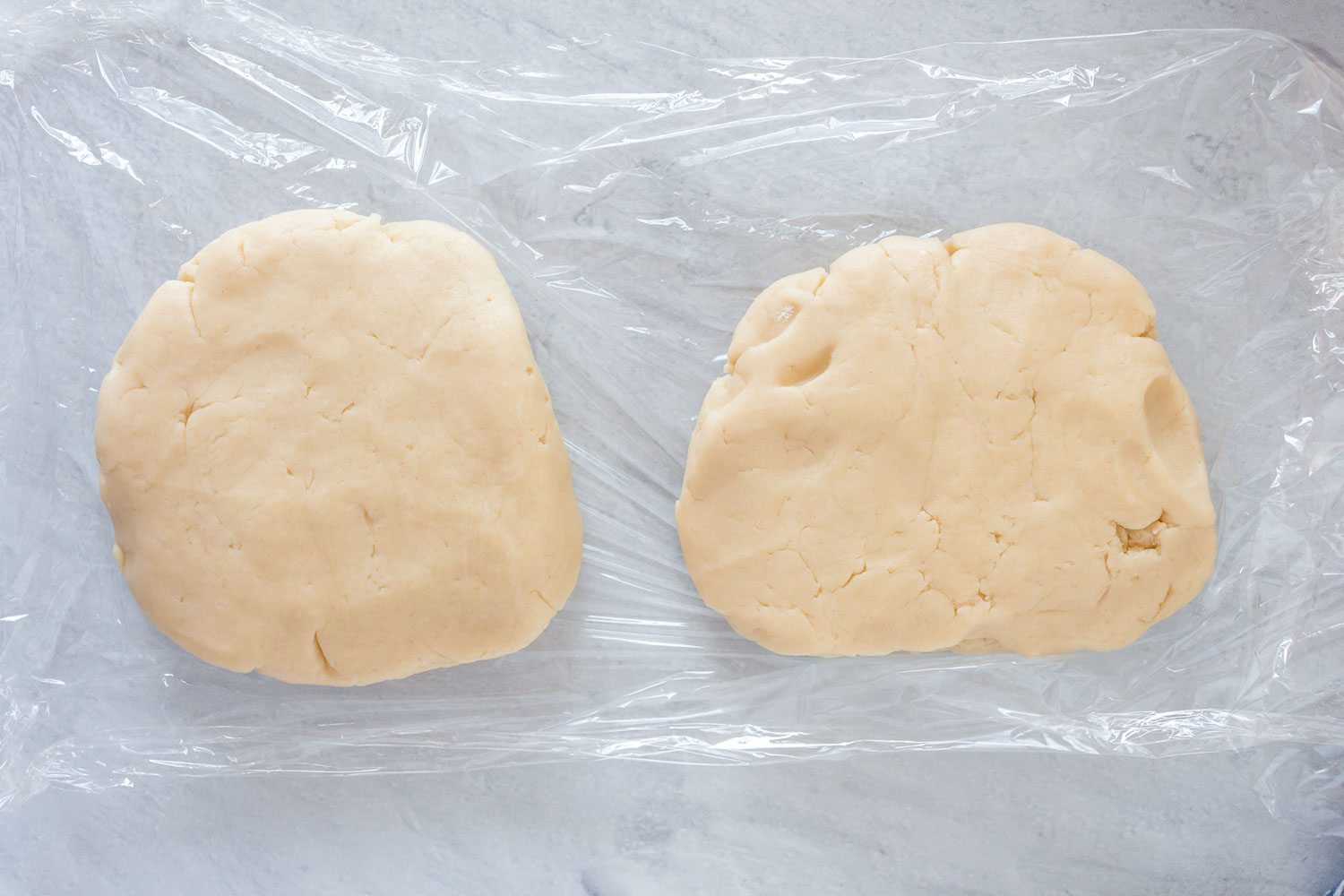 Two slabs of dough on plastic wrap.
