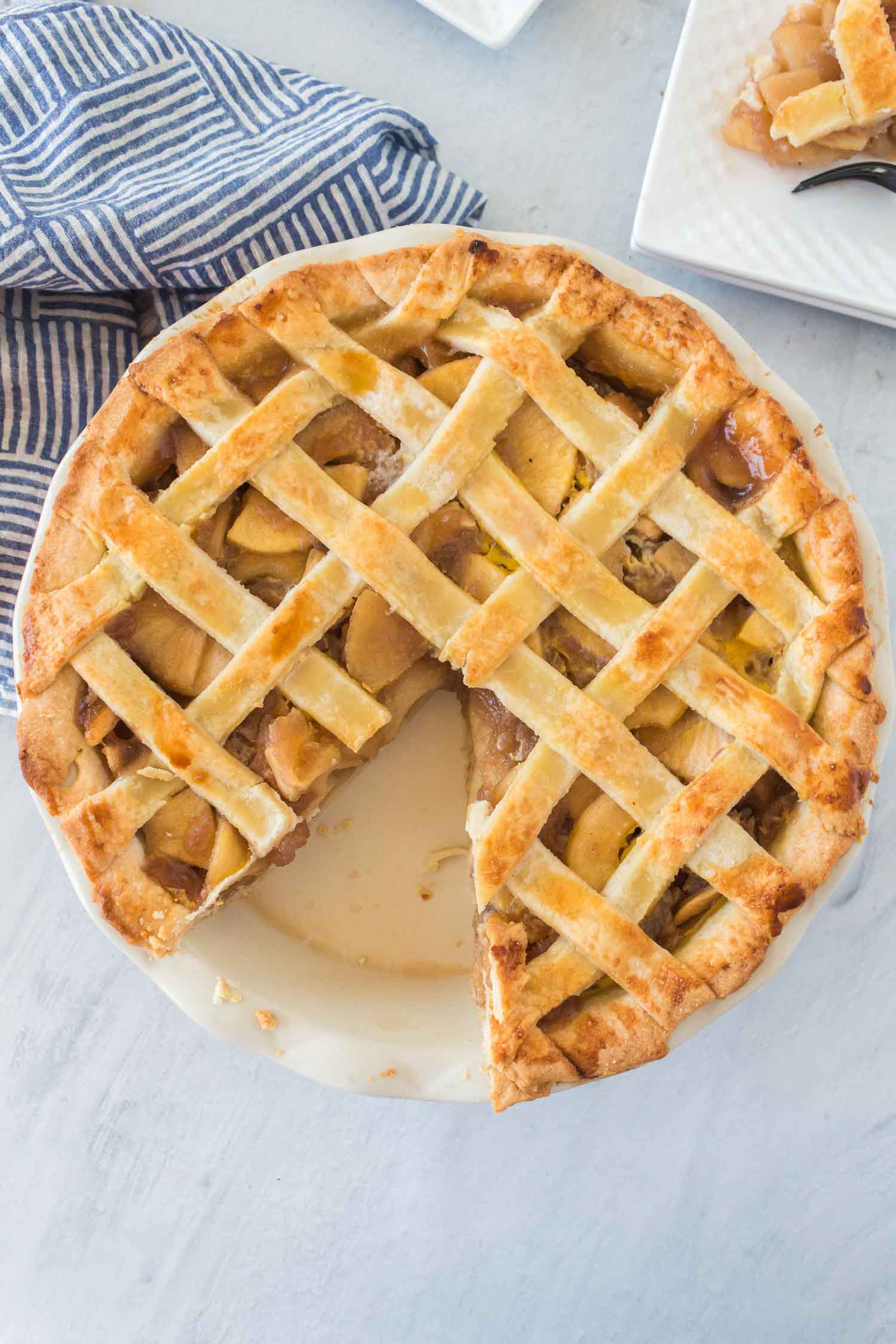 An apple pie with a slice cut out of it on a white plate in the background with a blue and white striped towel.