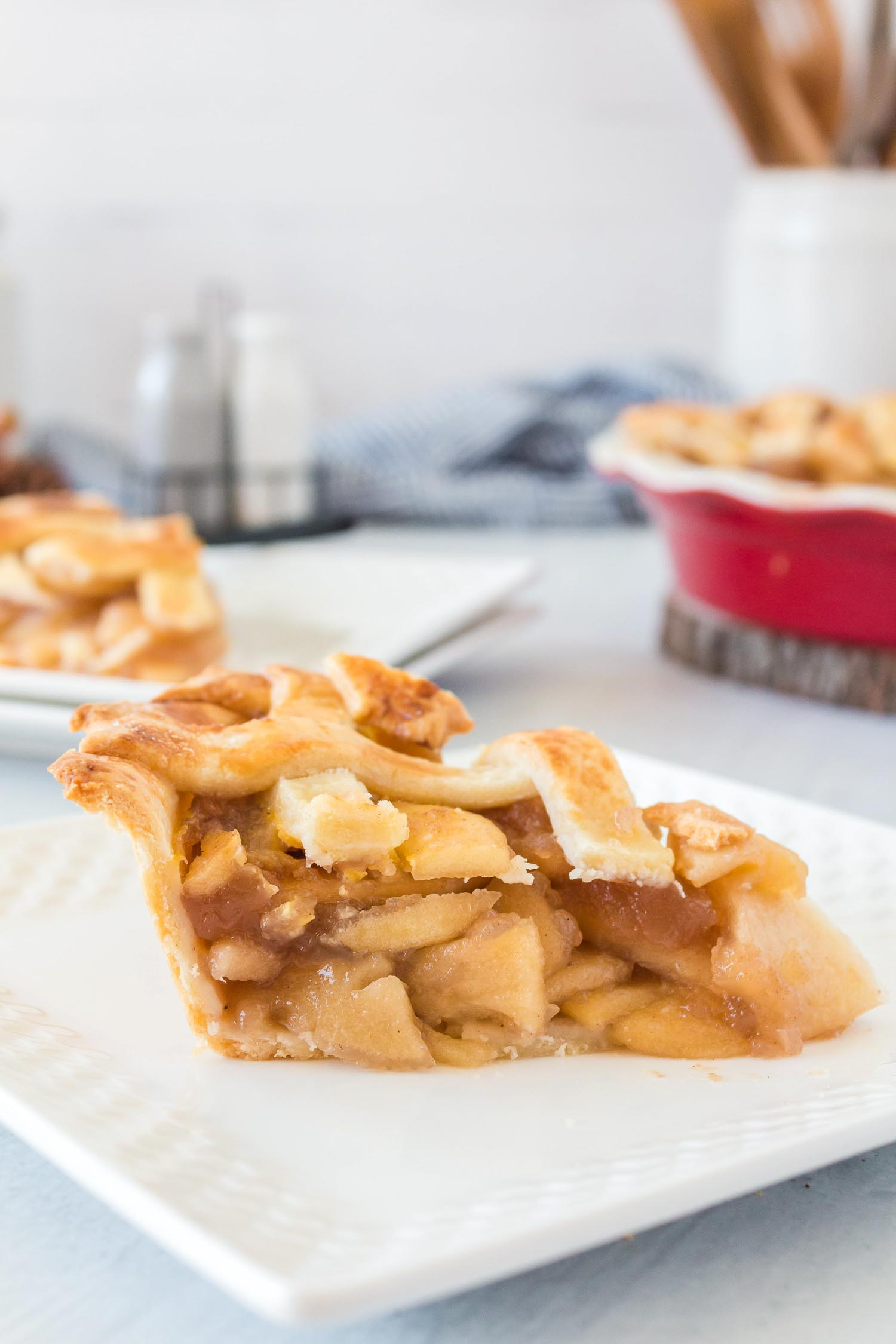 A slice of homemade apple pie on a white plate with apple pie in the background.