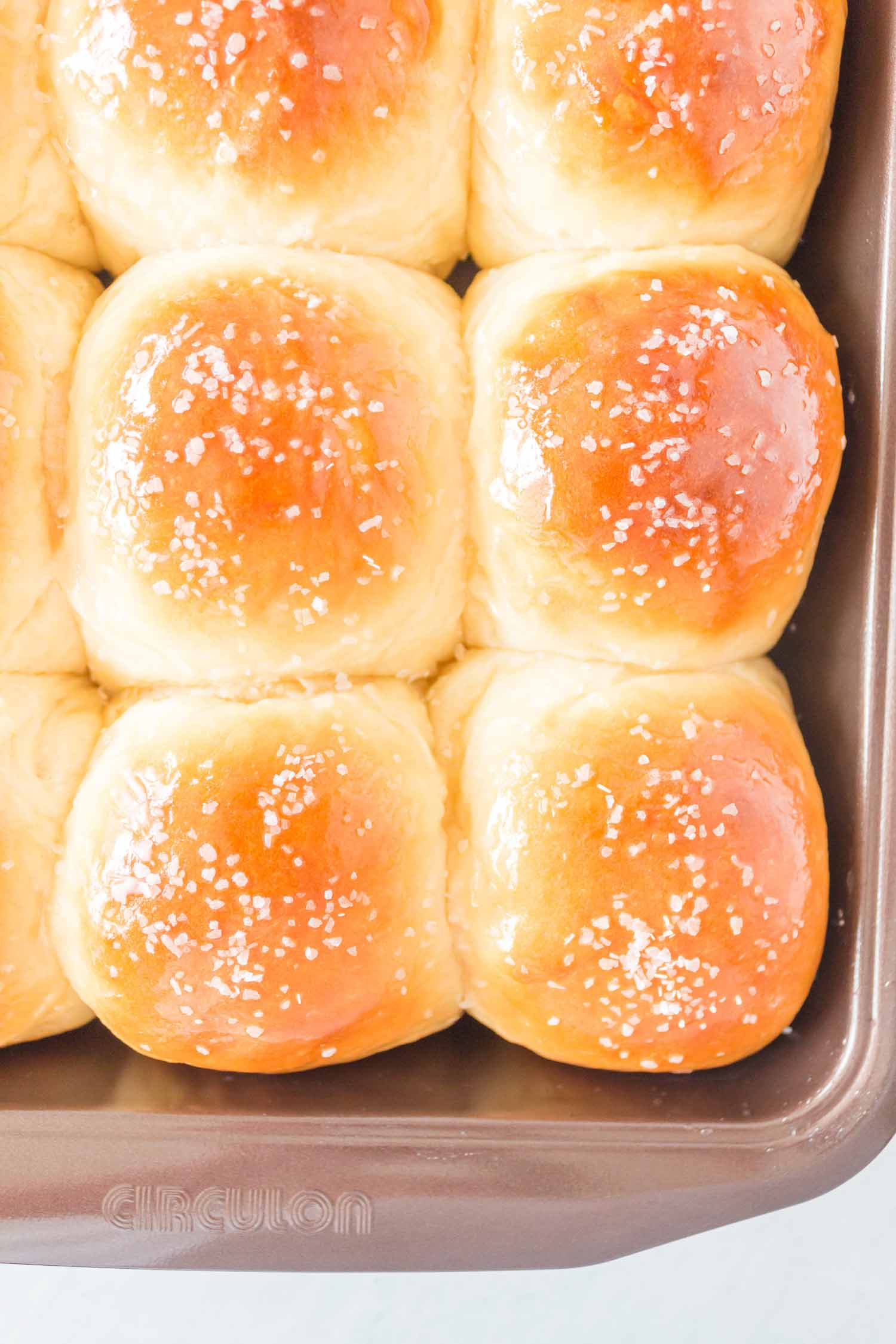 Cooked rolls that have been buttered and salted in a dark nonstick pan.