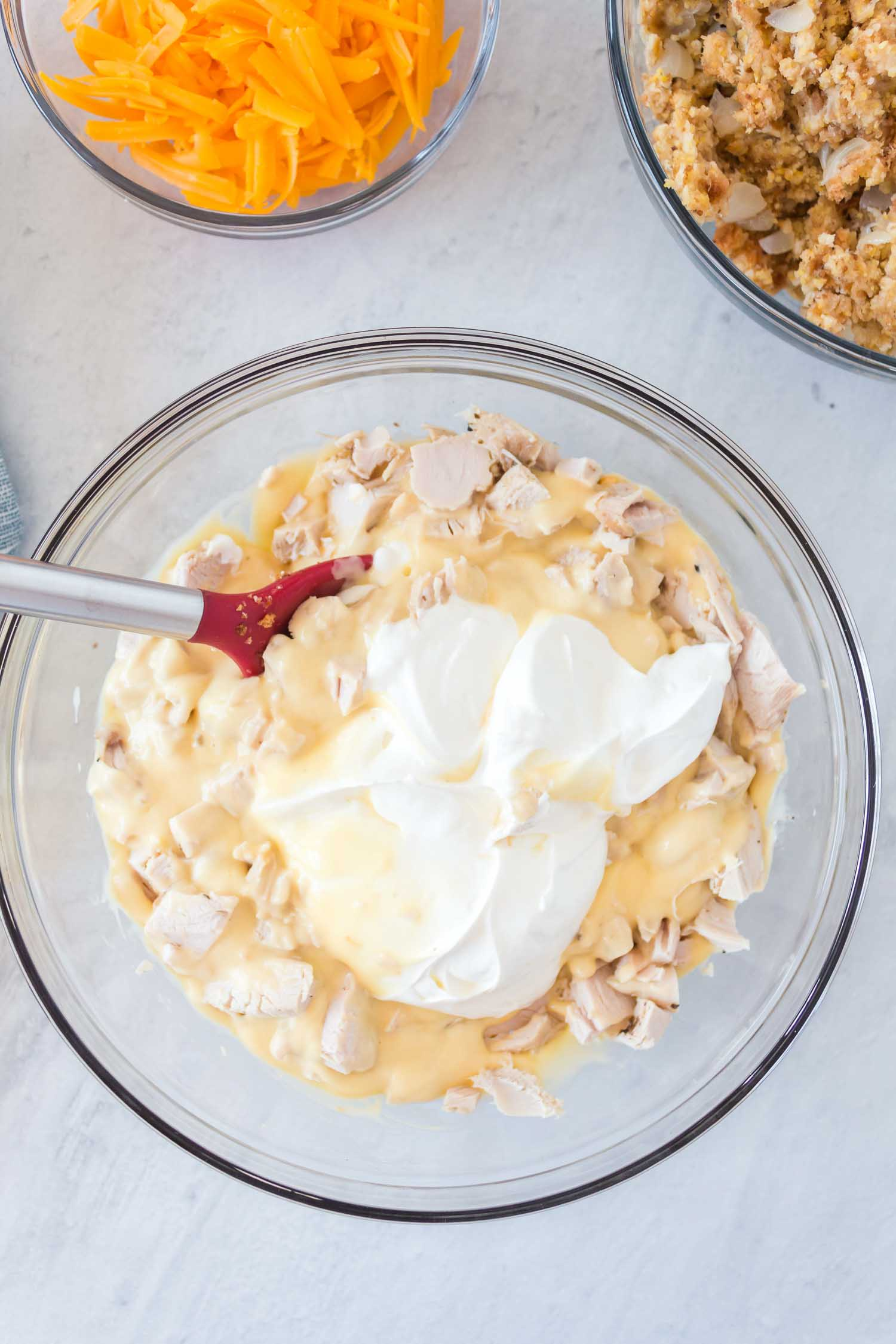 A glass bowl with turkey, gravy and sour cream with a red and metal spoon inside of it with a bowl of grated cheese and a bowl of stuffing behind it.