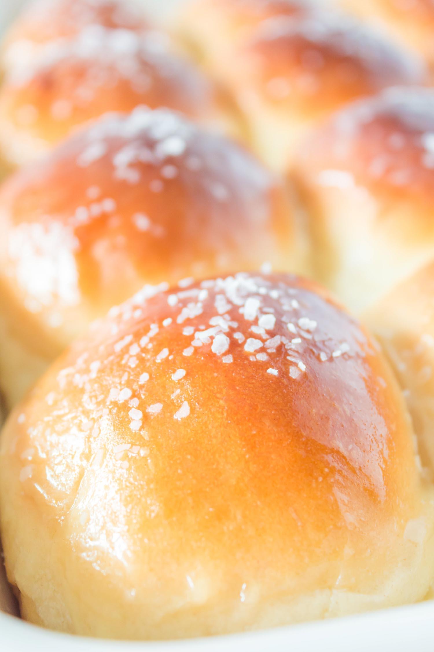 A closeup of buttered, salted dinner rolls
