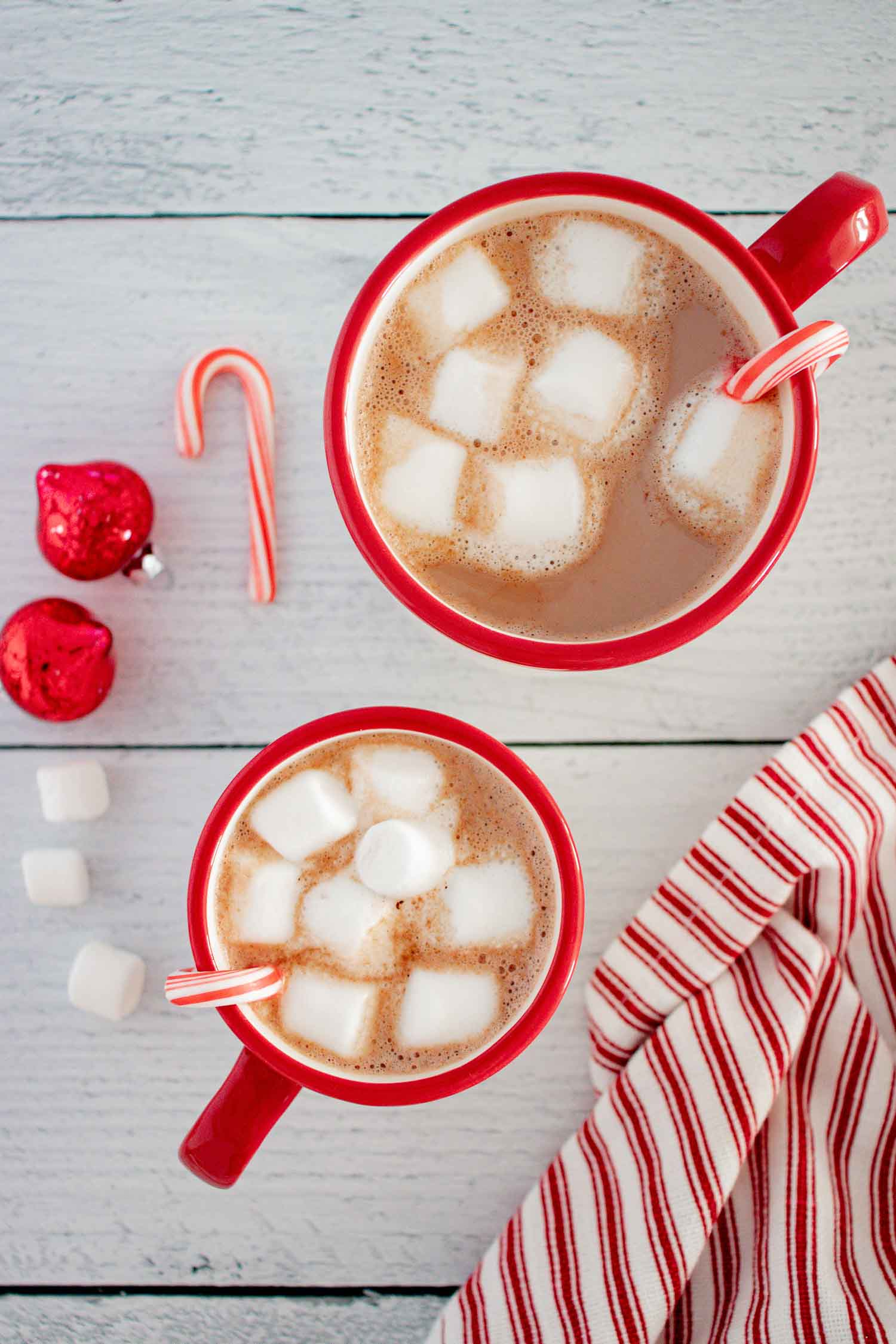 Two red mugs with filled with hot chocolate and marshmallows with a candy cane hanging off the side of the mug and candy canes and ornaments around it.