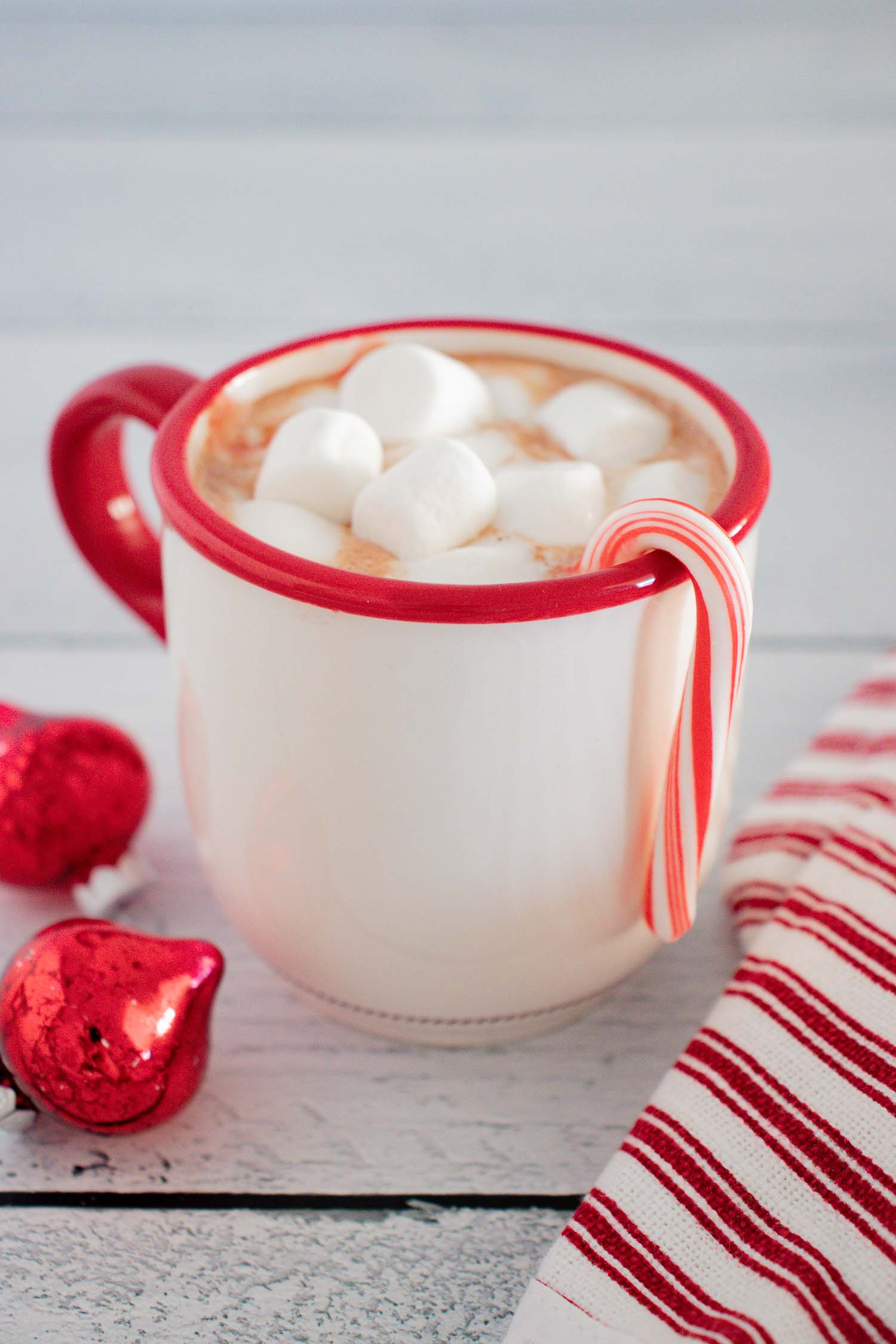 A white cup with a red rim filled with hot chocolate and marshmallows with a candy cane hanging off the side.