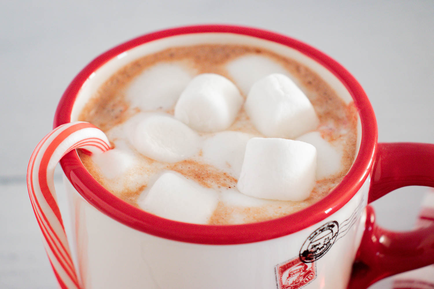 A white cup with a red rim filled with hot chocolate with marshmallows inside with a candy cane hanging off the side.