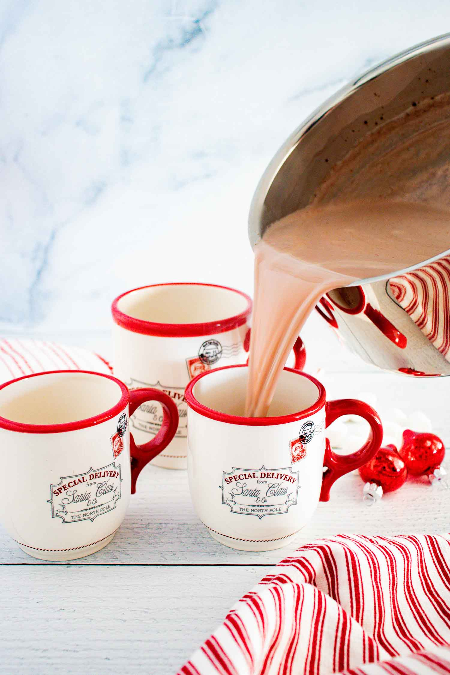 A metal pot pouring hot chocolate into a white mug with writing with a red handle and rim.  There are two other similar mugs next to it.