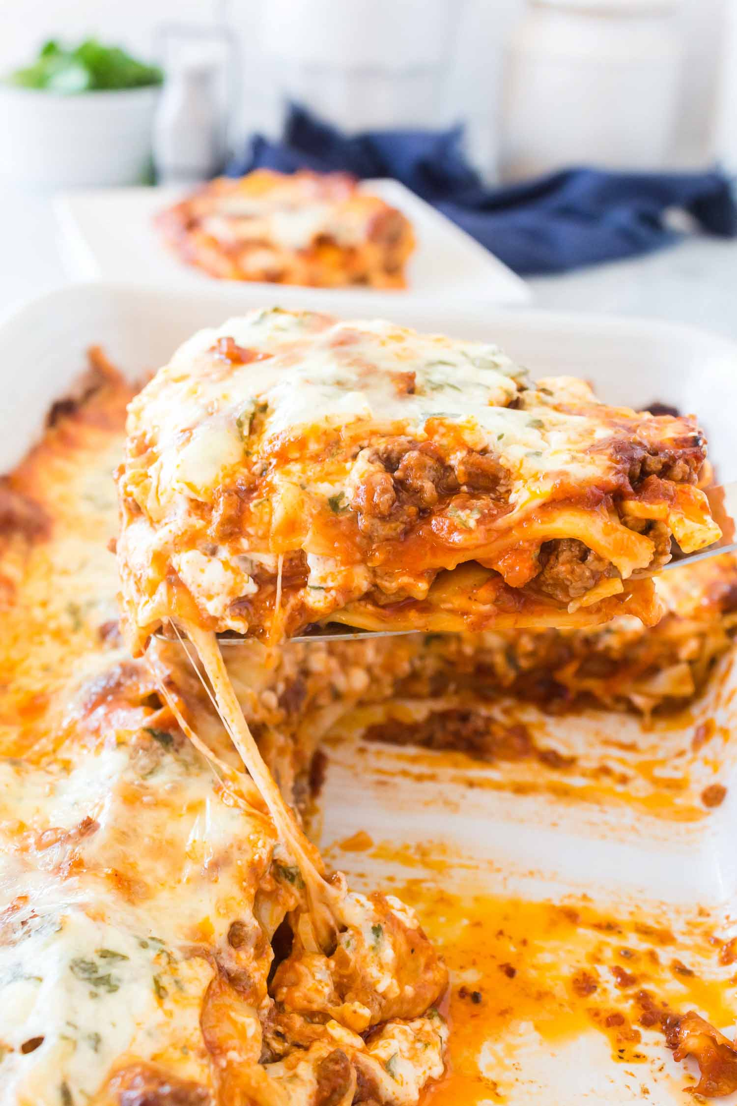 A white dish of lasagna with a serving taken out with a metal spatula.