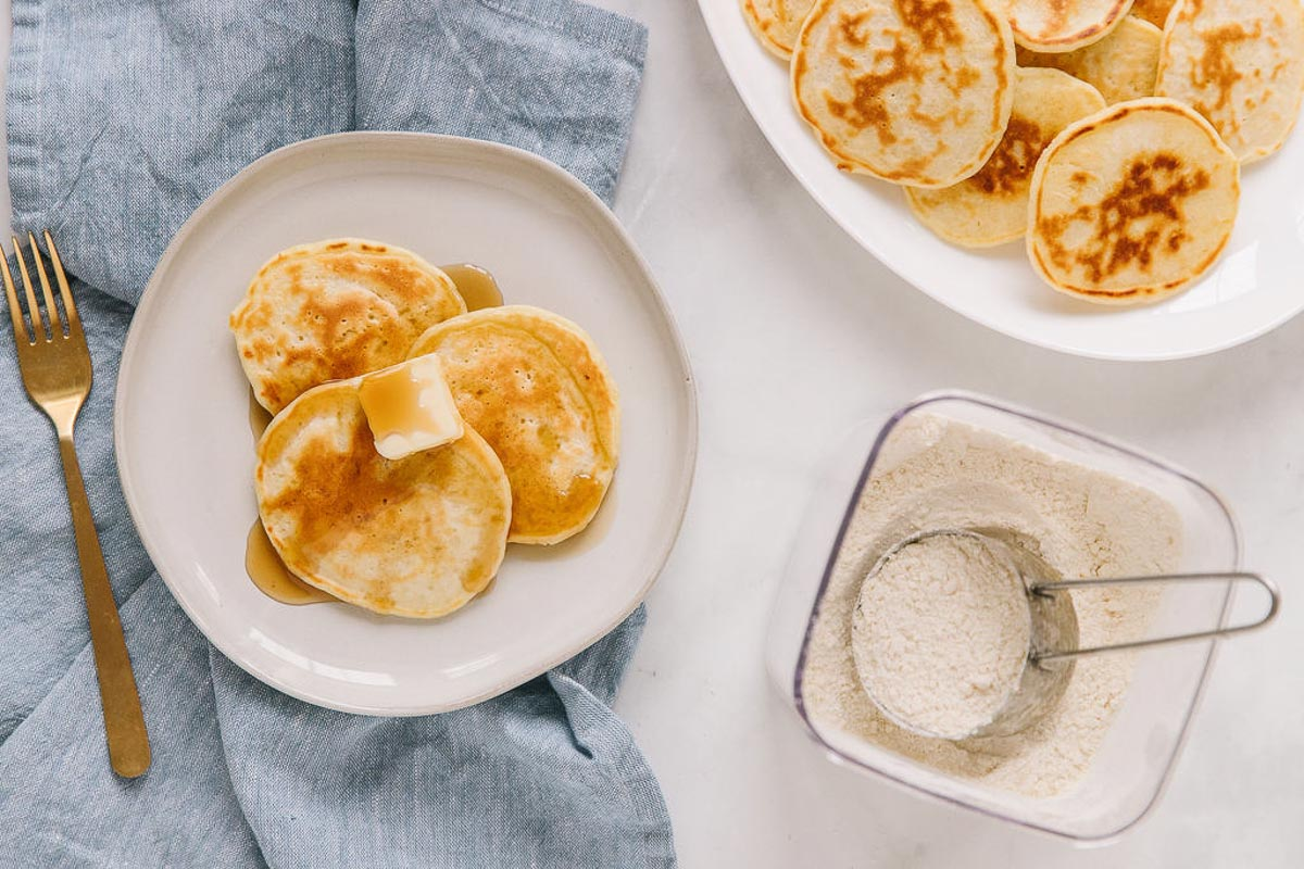 A white plate with pancakes, a pat of butter and syrup on it with a gold fork on a blue tablecloth next to a white platter of more pancakes and a plastic canister of mix with a measuring cup in it.