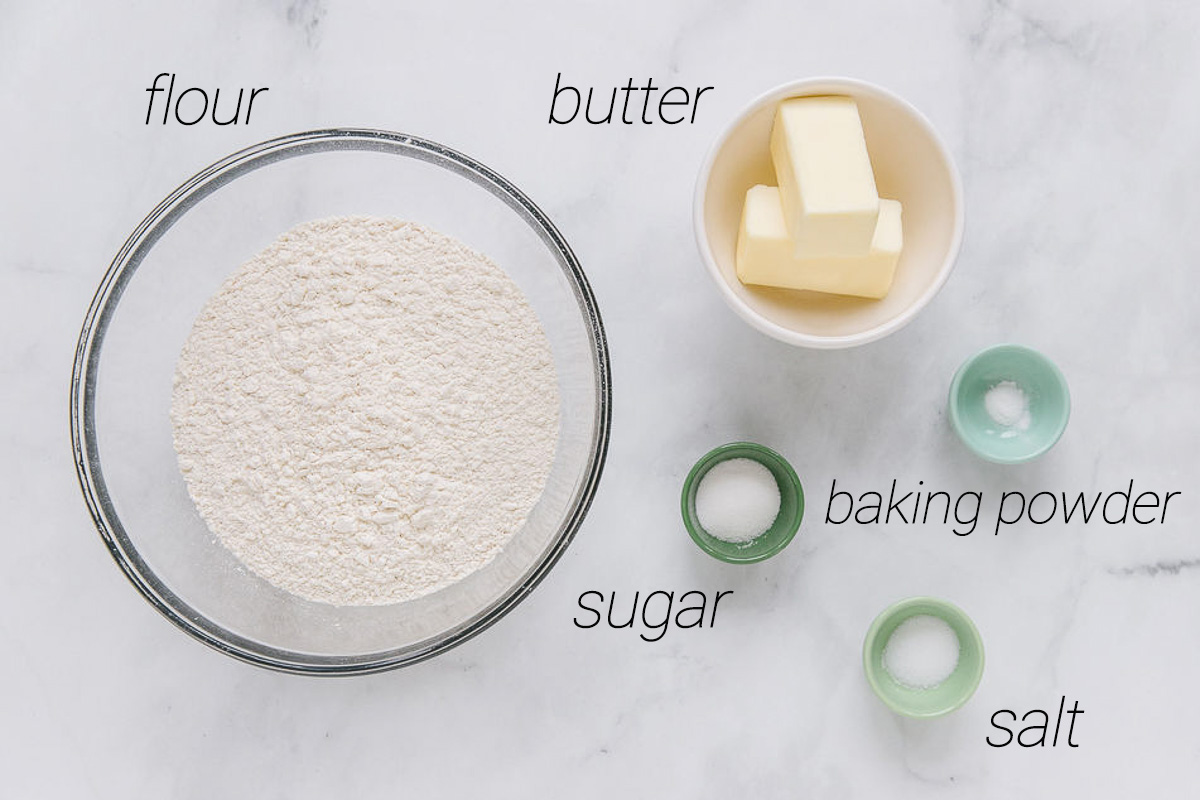 A glass bowl with flour in it and smaller colored bowls with butter, baking powder, sugar and salt in them.