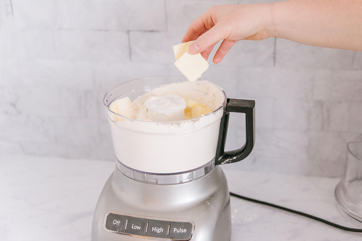 A food processor with dry ingredients in it with a hand adding butter into it.