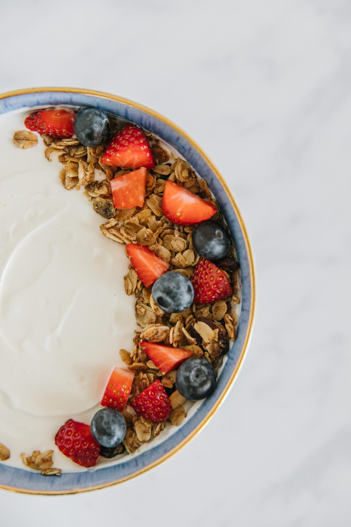 Half of a blue-rimmed bowl of yogurt with fruit and granola on it.