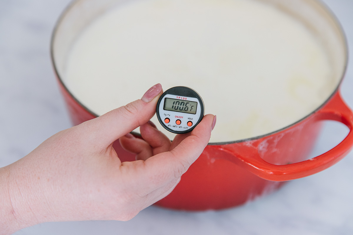 An orange Dutch oven filled with a white mixture with a thermometer reading 100.6 degrees in it with a hand holding it up.