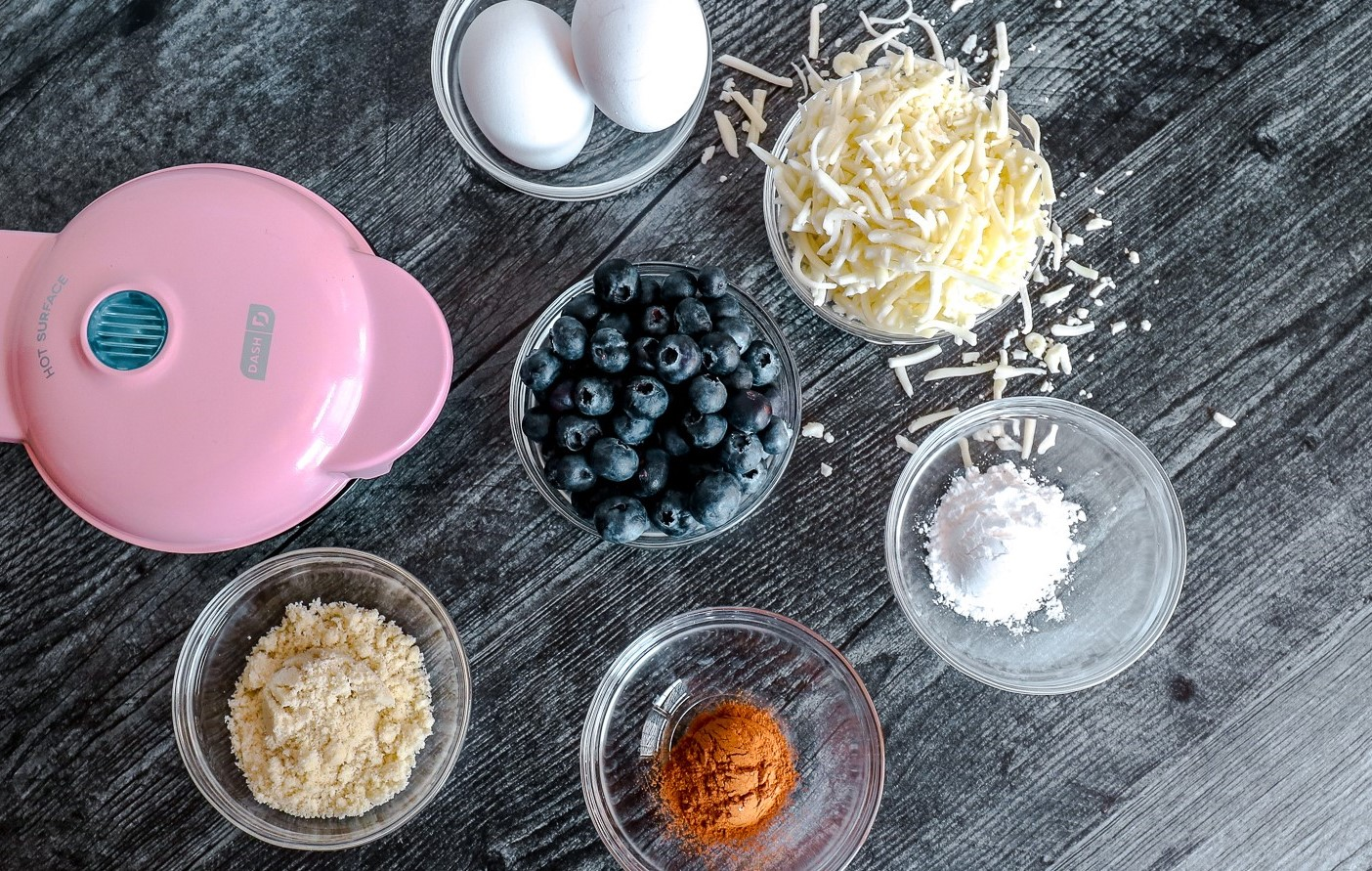 A pink waffle maker and ingredients in glass bowls of: eggs, almond flour, blueberries, cinnamon, cheese and swerve.