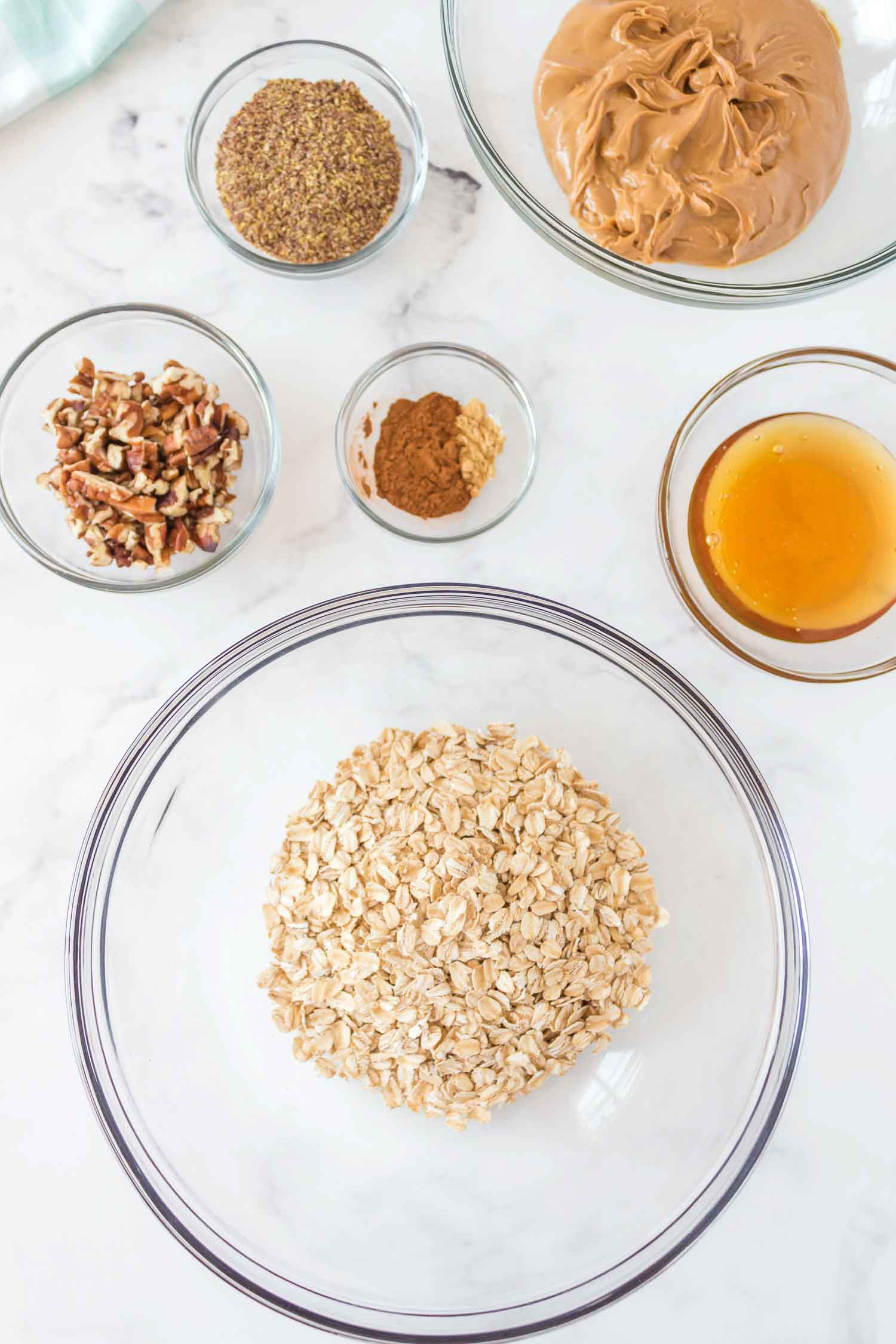Glass bowls filled with different ingredients: peanut butter, honey, spices, pecans, flaxseed, and oatmeal.