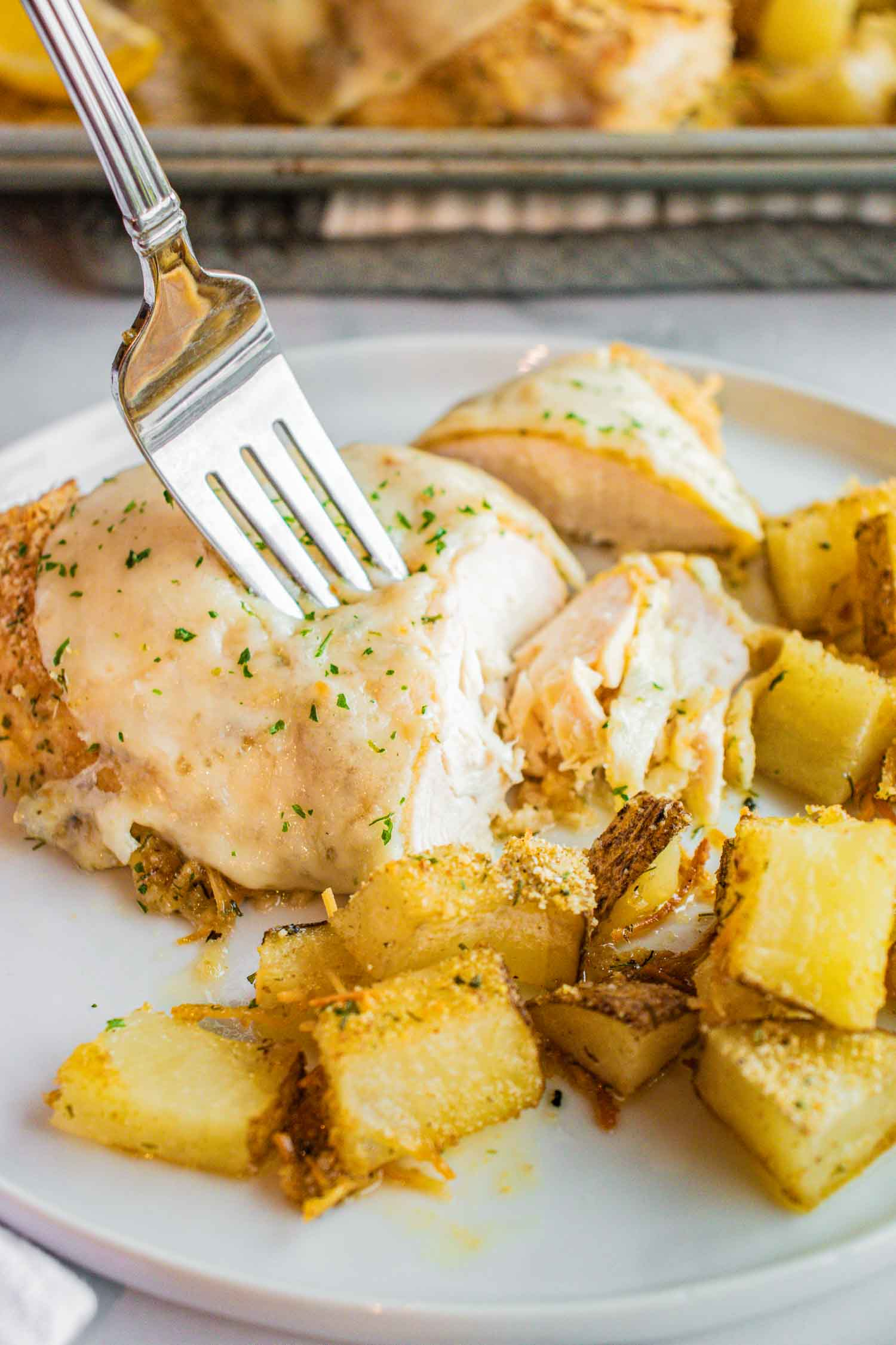 A white plate with cooked cut chicken and cooked potatoes with a fork in it and there is a metal pan behind it.