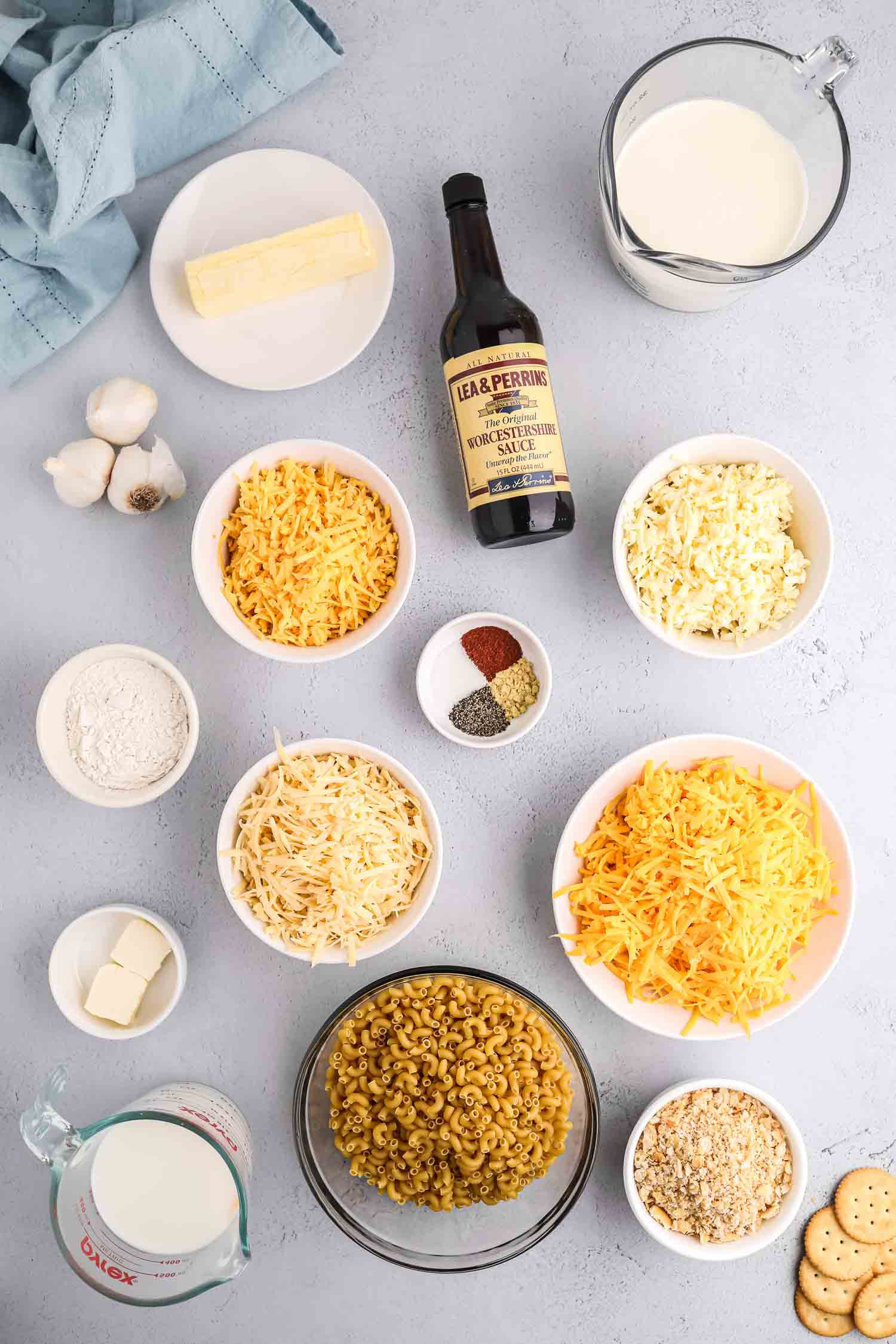 White bowls with ingredients of macaroni and cheese with bulbs of garlic, Worcestershire sauce, cream and butter.