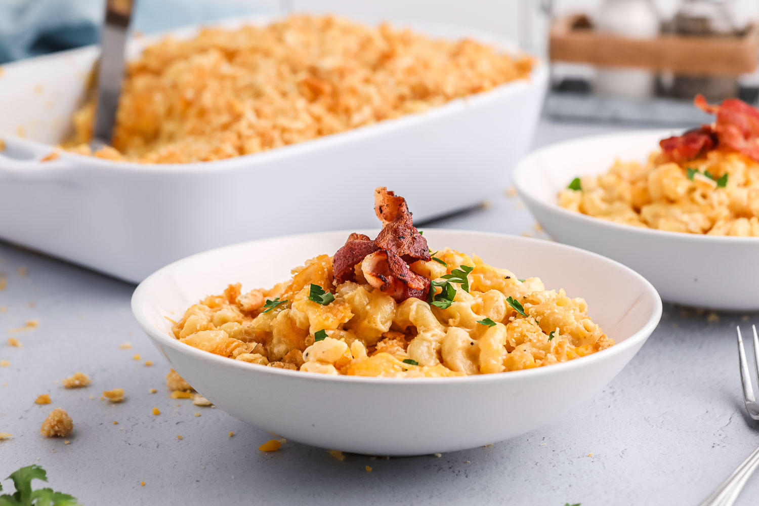 Two white bowls of mac and cheese with bacon on it and a large pan of mac and cheese behind it with a spatula in it and a fork on the side.