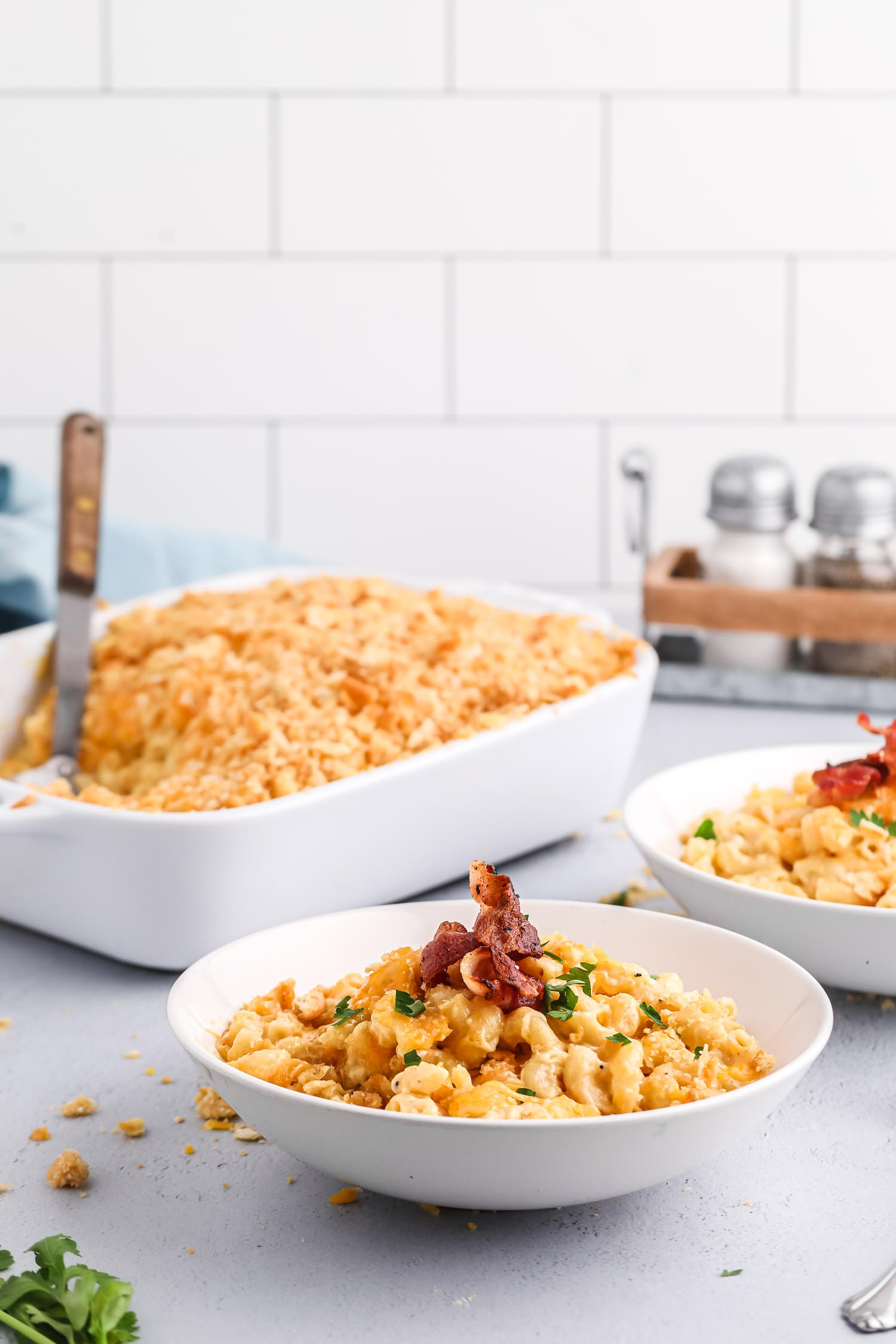 Two white bowls of mac and cheese with bacon on it and a large pan of mac and cheese behind it with a spatula in it.
