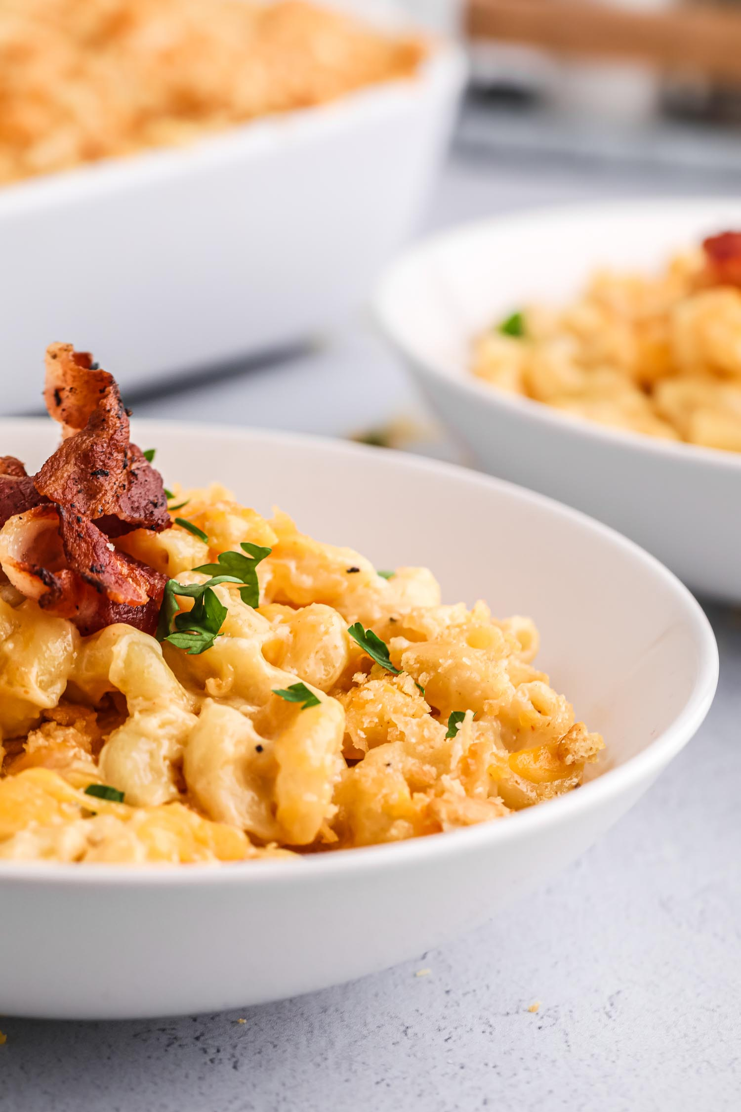 Two white bowls of mac and cheese with bacon on it.
