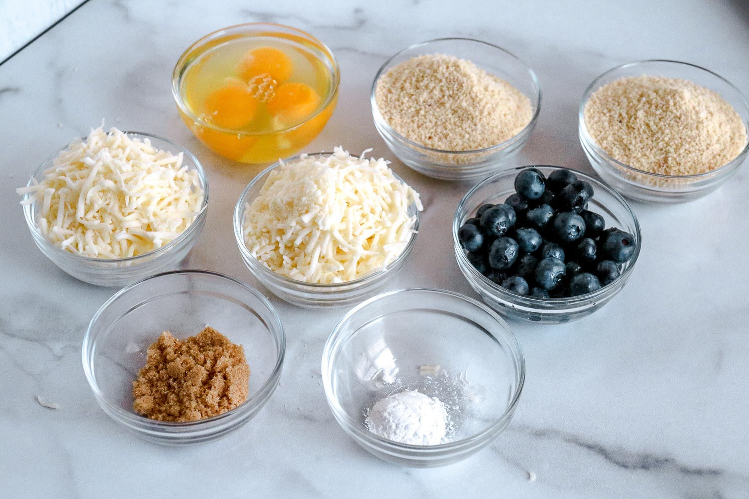 8 small glass bowls full of eggs, almond flour, mozzarella cheese, swerve, blueberries and baking powder.
