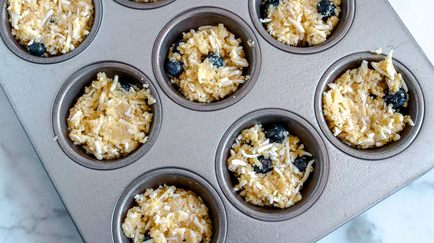 A muffin pan with uncooked keto muffin batter in it.
