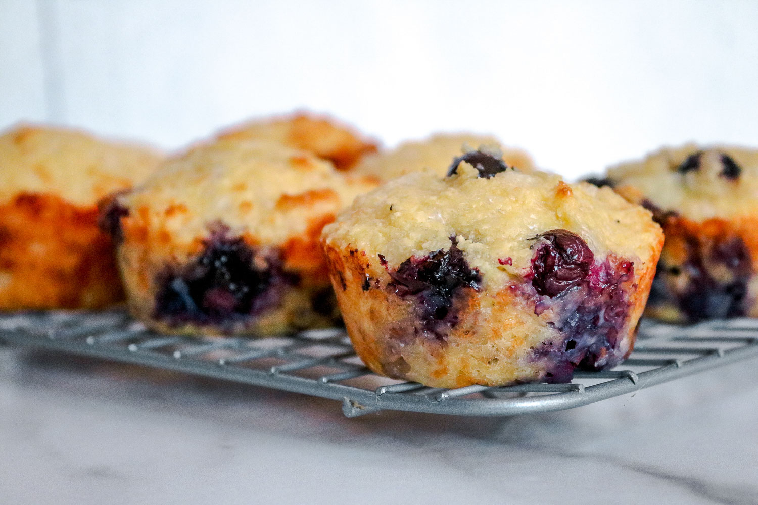 A wire rack with blueberry muffins on it.