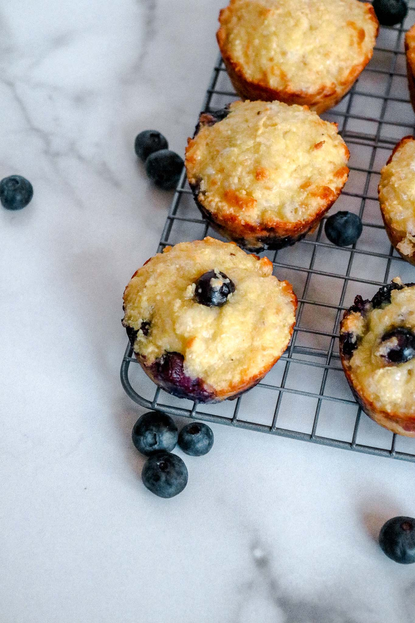 A wire rack with cooked keto blueberry muffins with scattered blueberries around it.