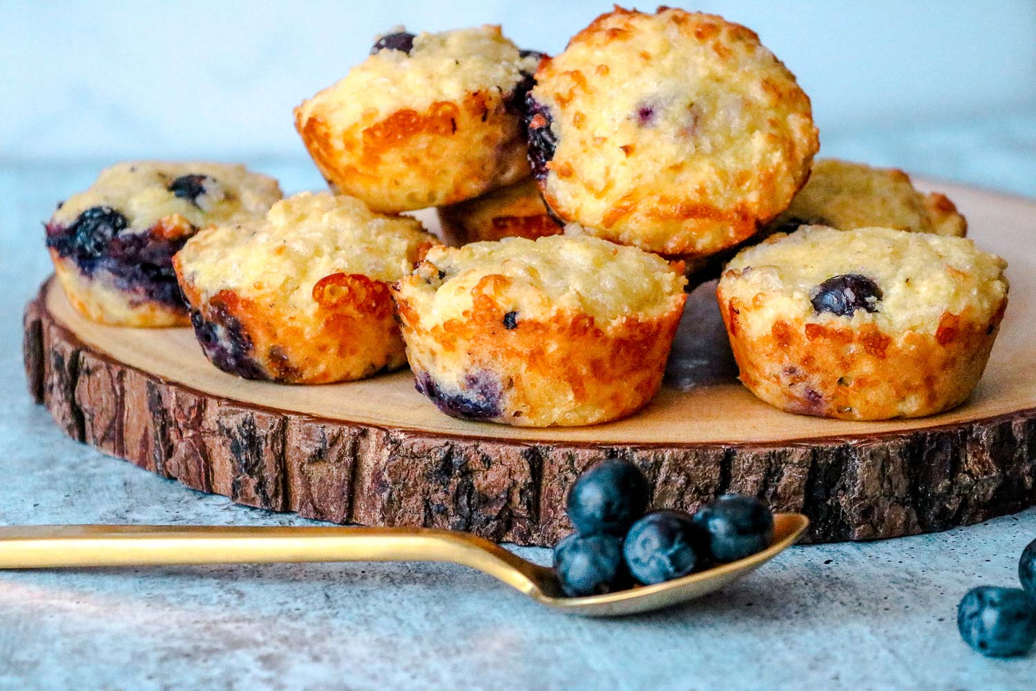 A wooden plan with blueberry low carb muffins stacked on it with a golden spoon with blueberry on it and around it.