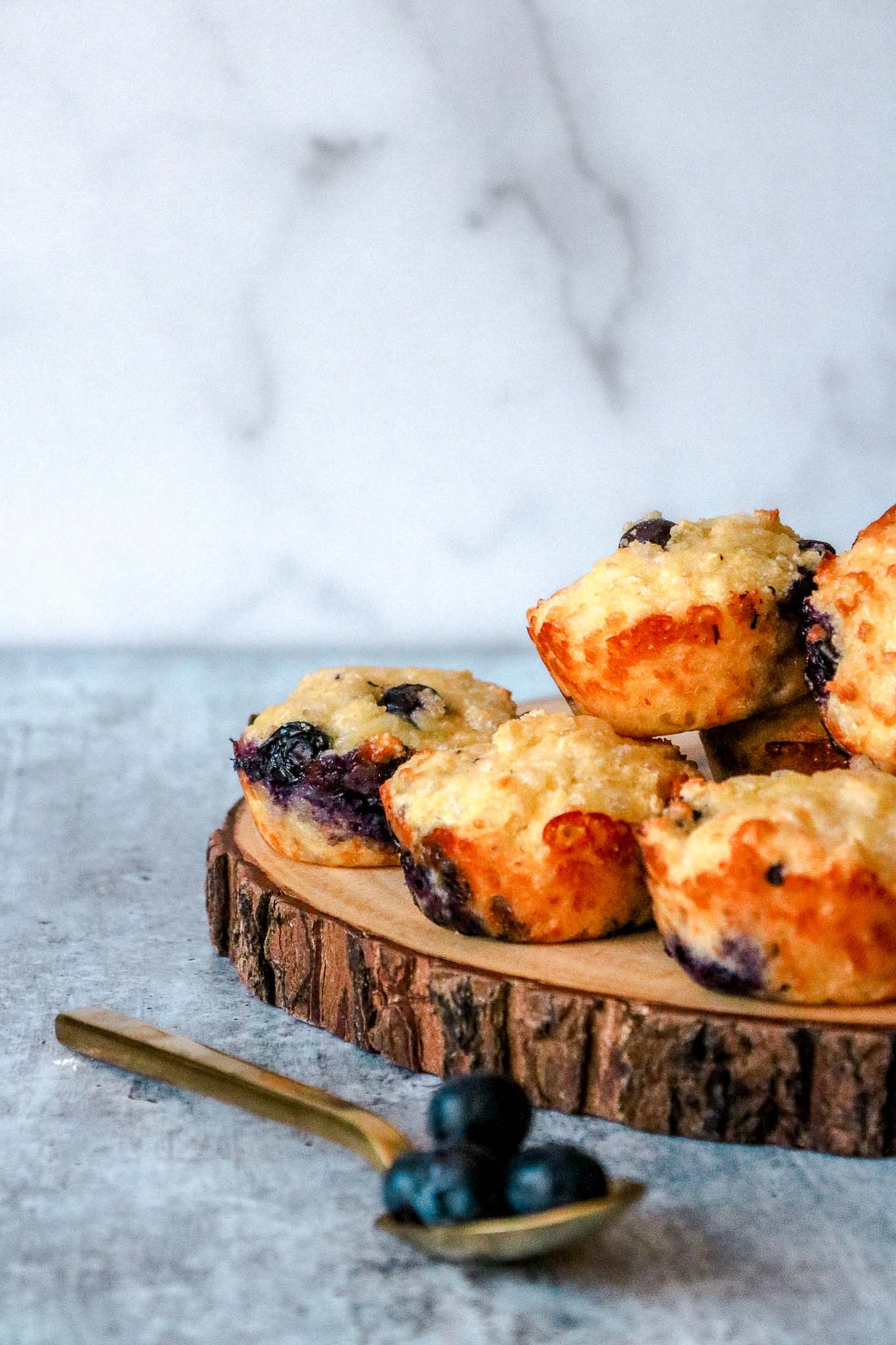 A wooden pedestal with muffins stacked on it with a gold spoon and blueberries on it in front.