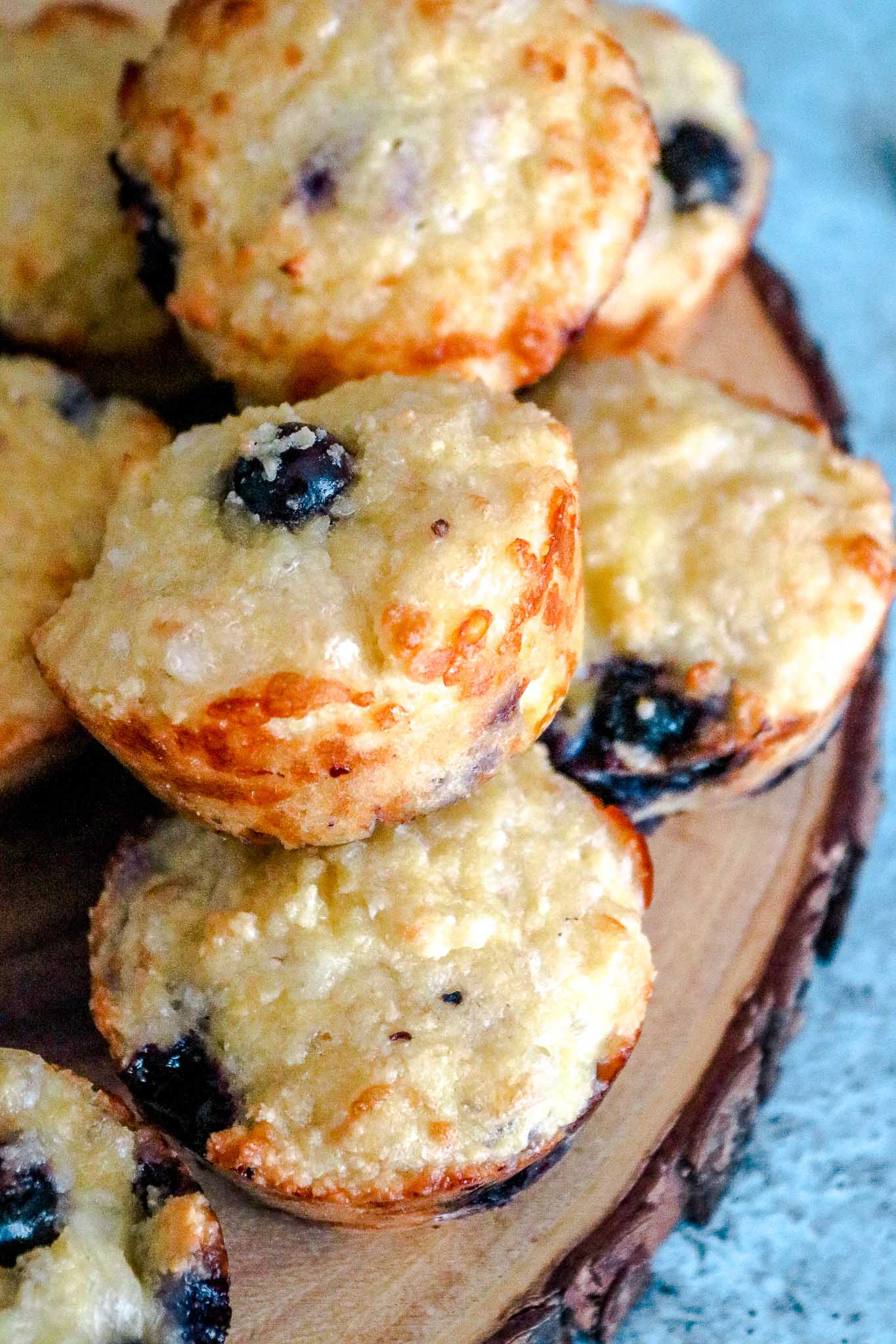 A wooden board with blueberry muffins stacked on it.