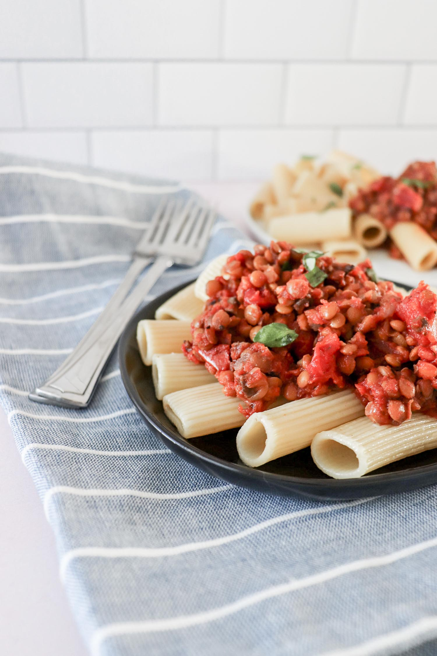 Two servings of pasta with Bolognese on it on white and black plates with two silver forks on a blue and white towel.