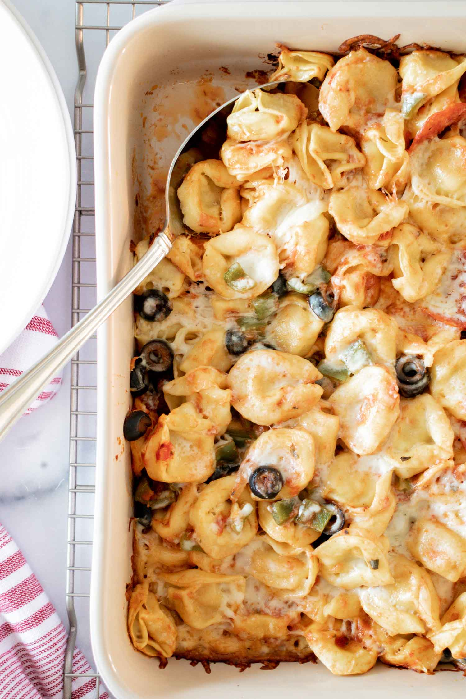 A white pan full of tortellini bake with a silver spoon in it on top of a wire rack.