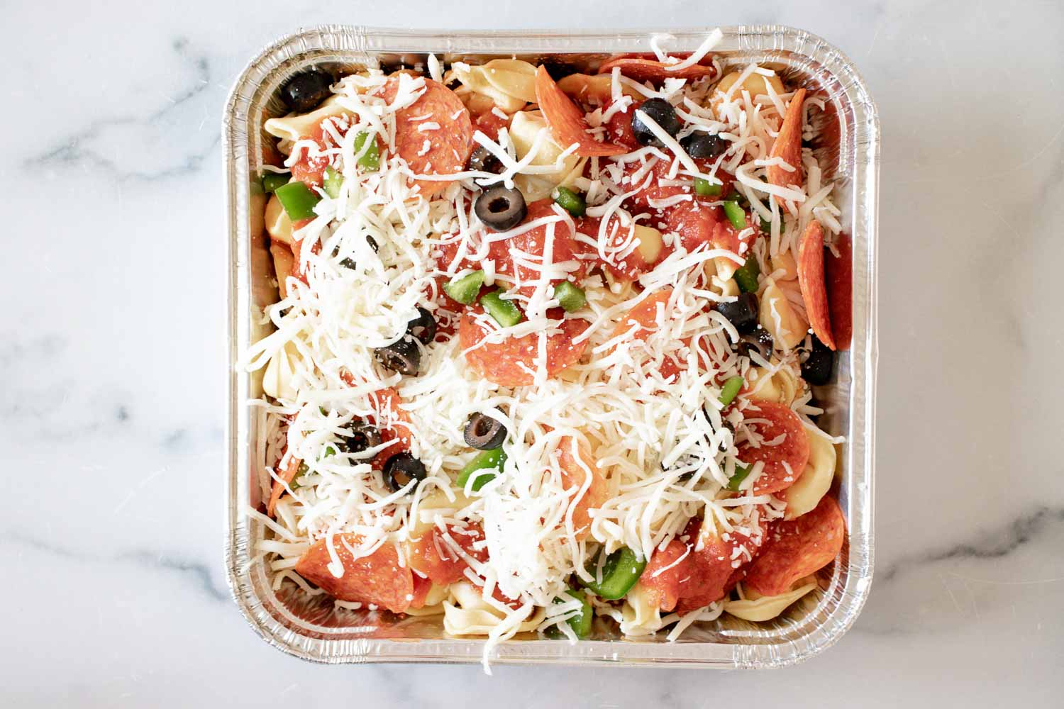 A silver square foil pan with unbaked pasta bake in it.
