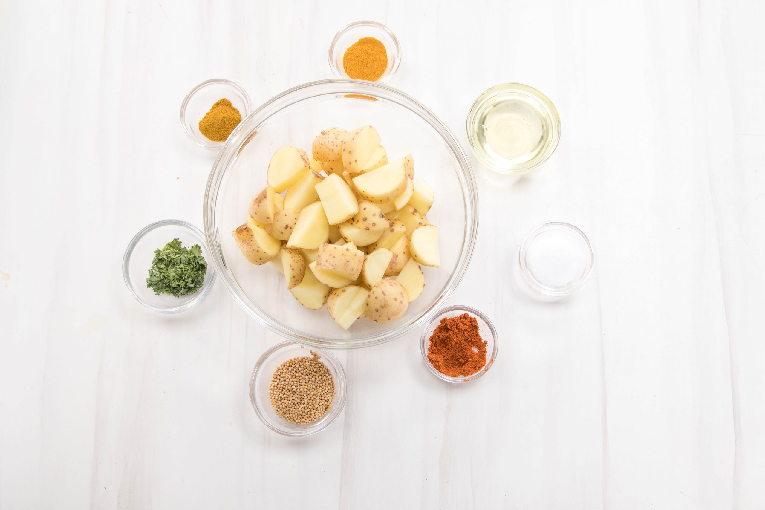 A white background with glass containers with spices and cut sliced potatoes in a big bowl in the middle