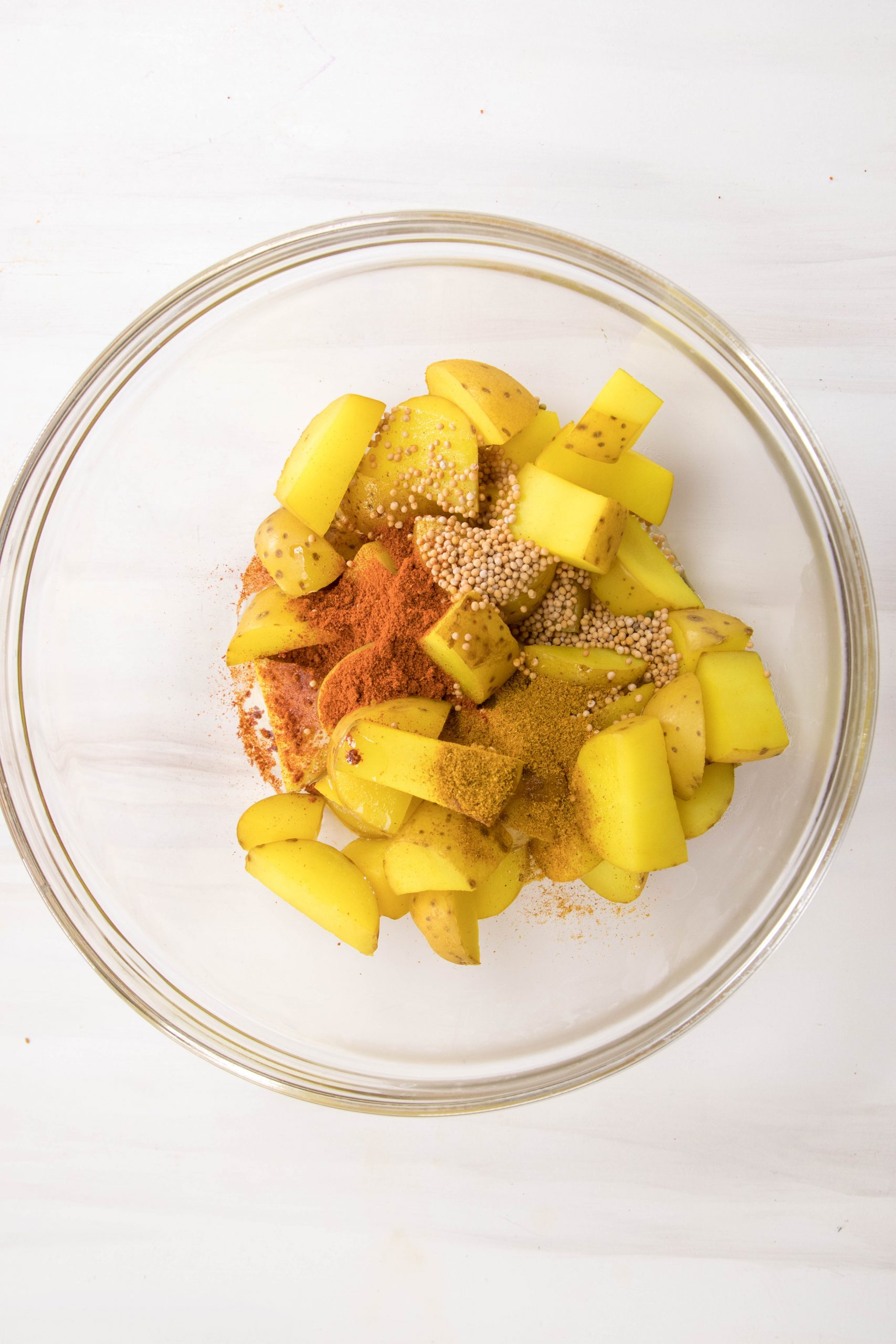 A glass bowl of cut potatoes and spices.