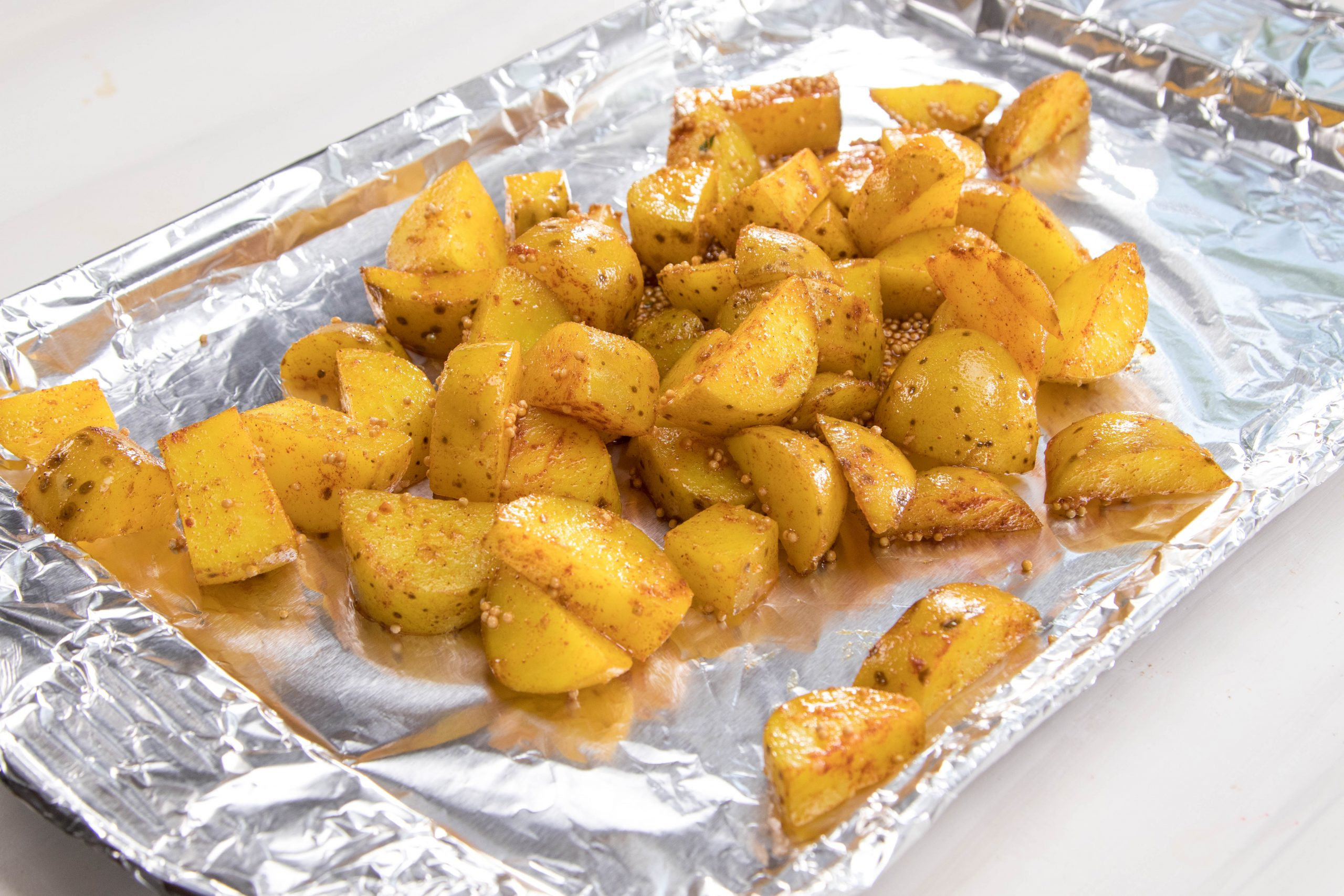 A foil-wrapped pan with seasoned, cut potatoes on it.