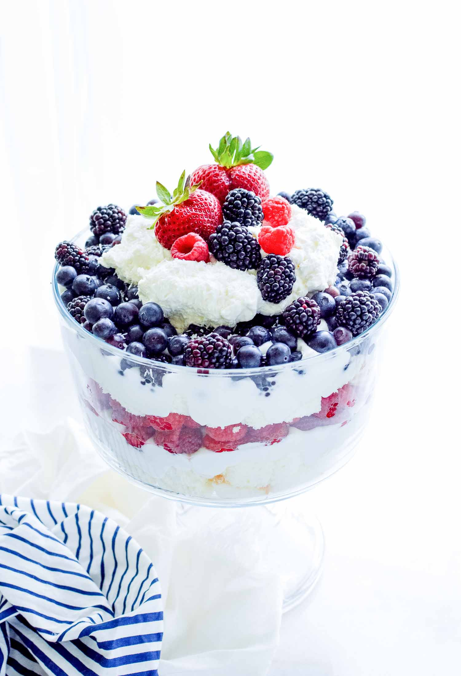 A clear glass trifle dish filled with cake, berries, and cream topped with cream and berries with a blue and white towel around the bottom.