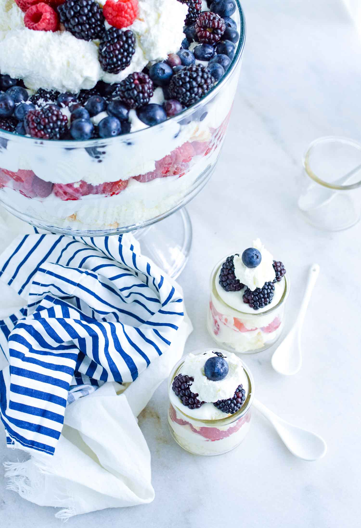 A clear glass trifle dish filled with cake, berries, and cream with a blue and white towel around the bottom and two filled glass cups and one empty glass cup with white spoons.