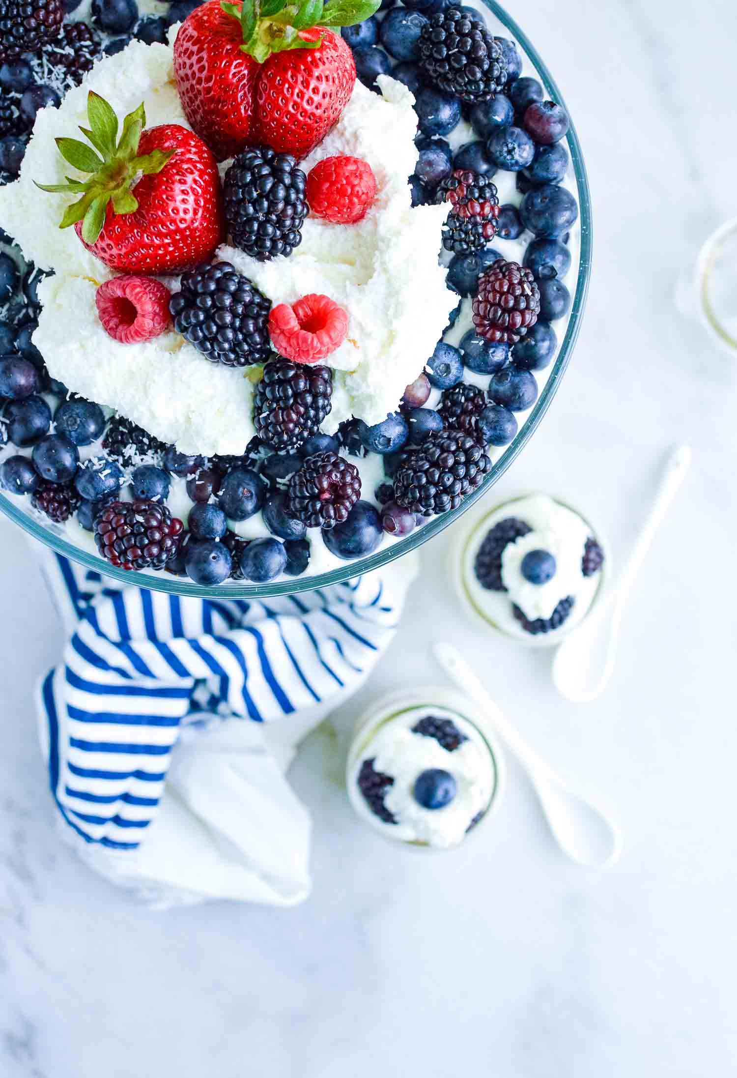A top look of a clear glass dish filled with cake, berries, and cream with a blue and white towel around the bottom with individual servings in glass cups and white spoons.