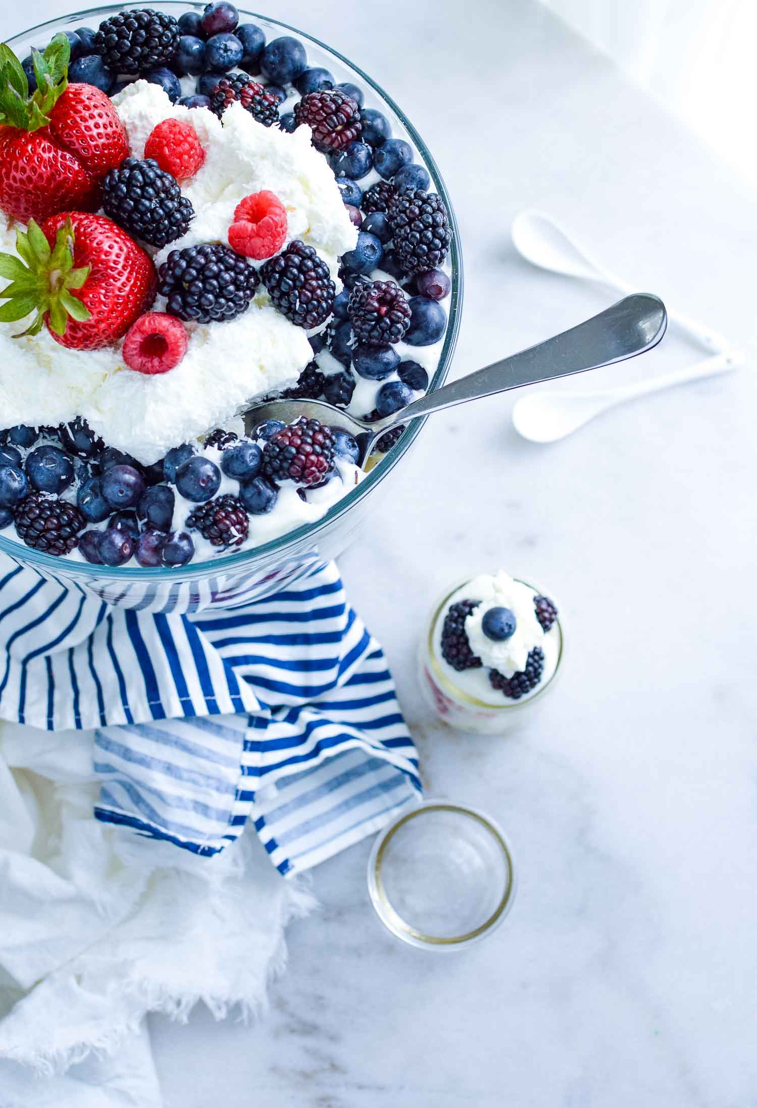 A clear glass dish filled with cake, berries, and cream with a metal spoon in it with blue and white towel around the bottom, two white spoons and two glasses - one full and one empty.