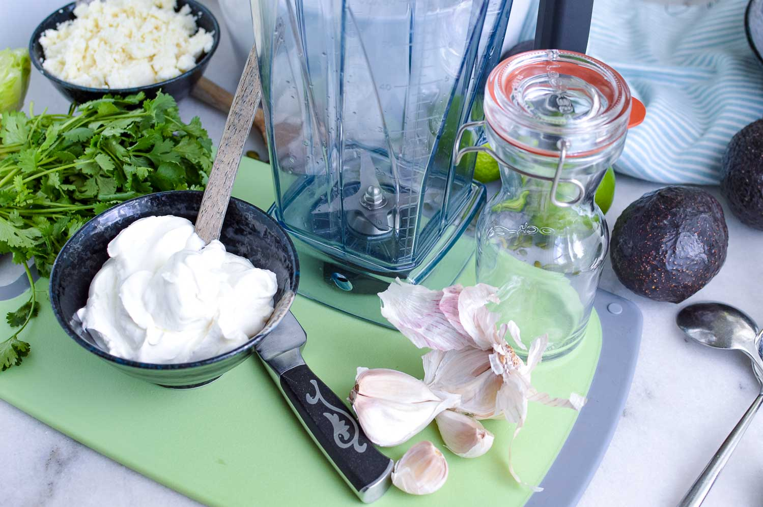 A blender and jar empty with ingredients on the green cutting board: sour cream. cilantro, cheese, garlic, lime, avocados with a knife on the side.