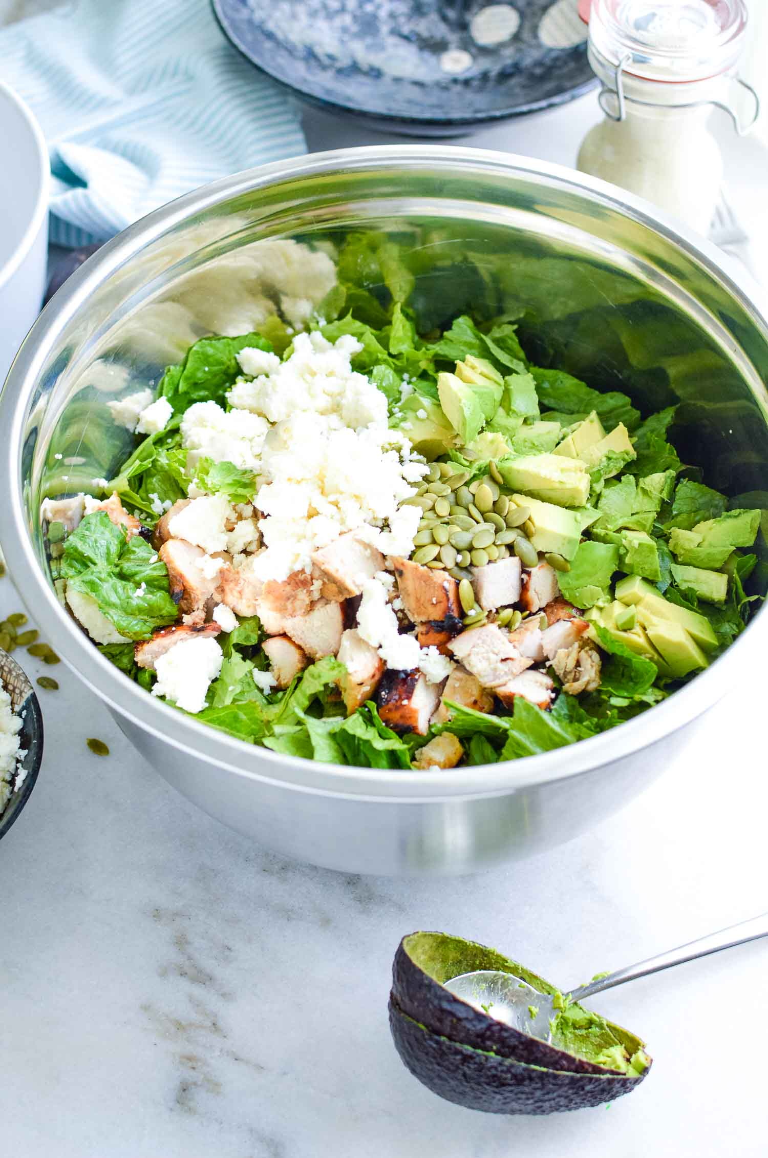 A silver metal bowl with lettuce, pumpkin seeds, chicken, avocados, and cheese with two empty avocado shells with a metal spoon in it.