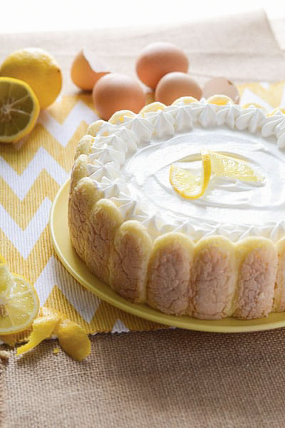 A whole cake on a yellow plate with a slice of lemon on top and also on the sides with whole eggs and cut lemons.