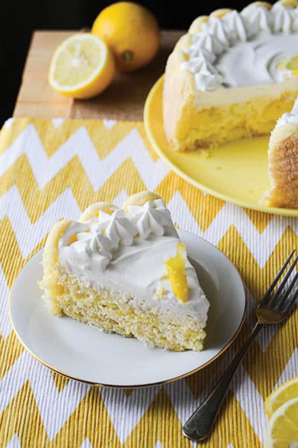 A cake on a yellow plate with a slice cut out of it and one slice on a white plate with a metal fork by it.